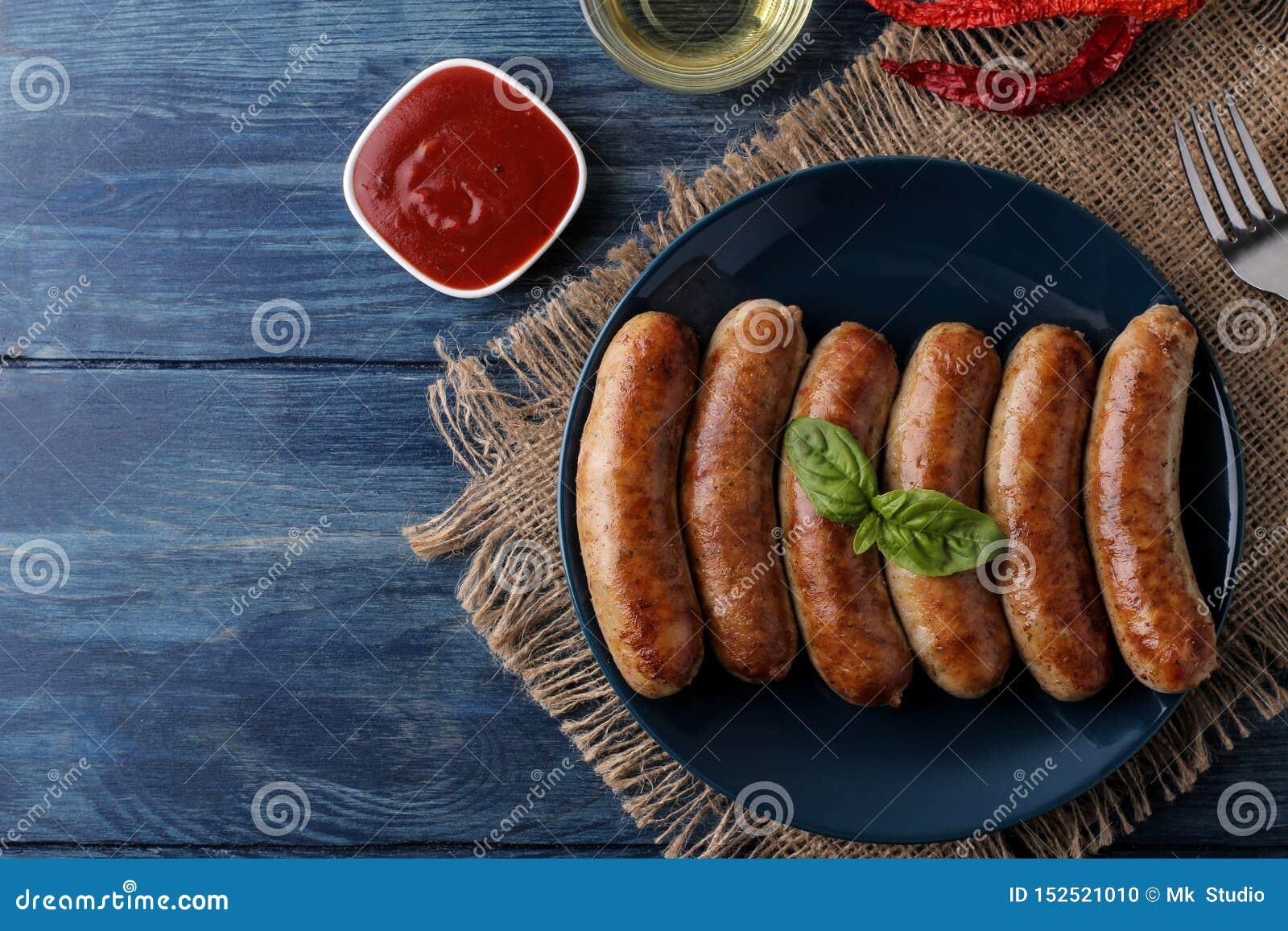 Salsiccie arrostite deliziose su un piatto con salsa e le spezie rosse su un fondo di legno blu B-B-Q Vista superiore