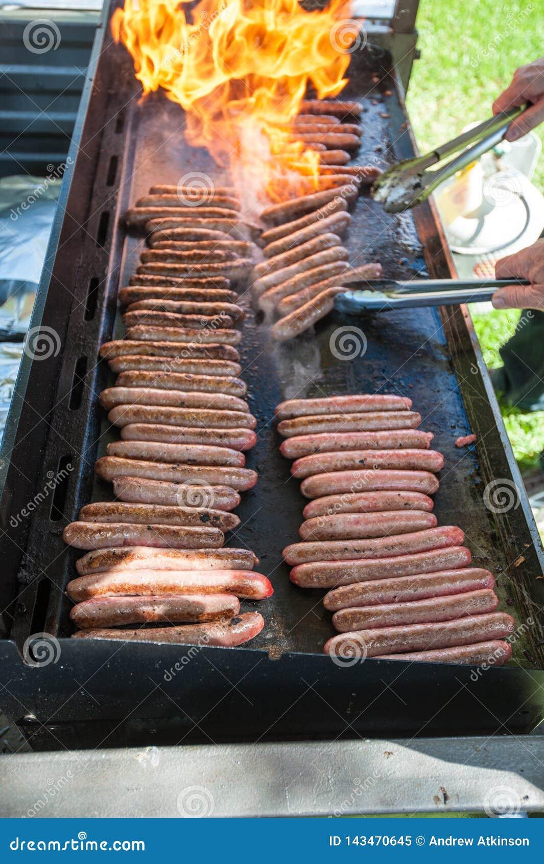 Salsiccie della griglia della fiamma su un barbecue
