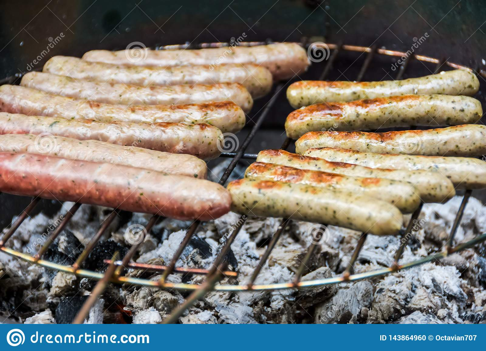 Salsiccie saporite multiple sulla griglia nella fine su