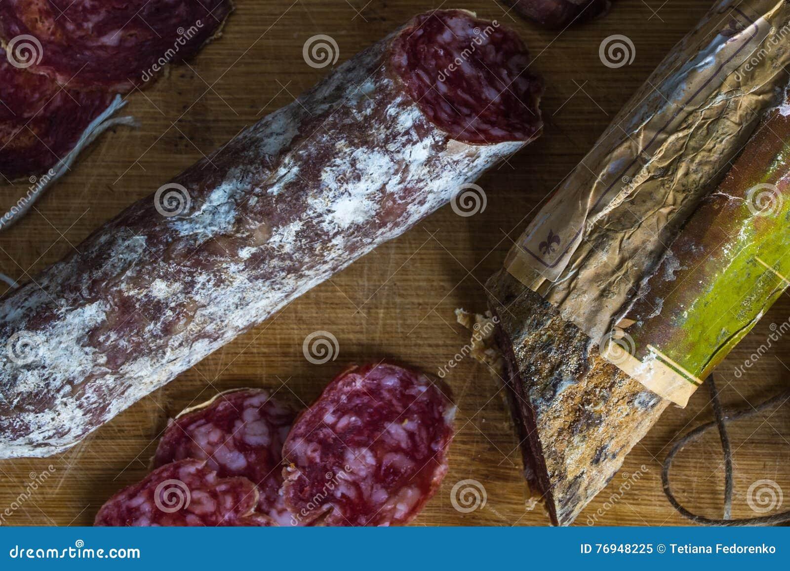 Salsicha secada & x28; Salami& x29; com o molde na placa de corte de madeira velha