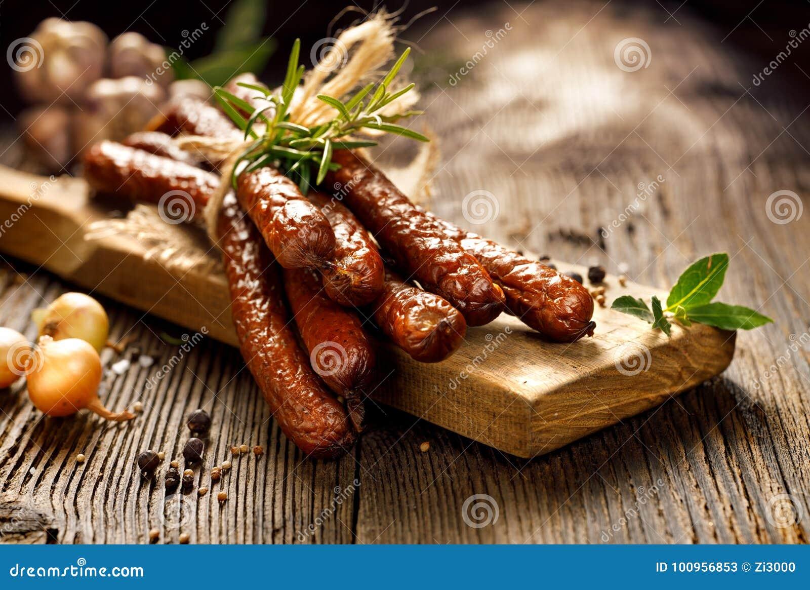Salsichas em uma tabela rústica de madeira com adição das ervas e das especiarias aromáticas frescas, produto natural da exploraç