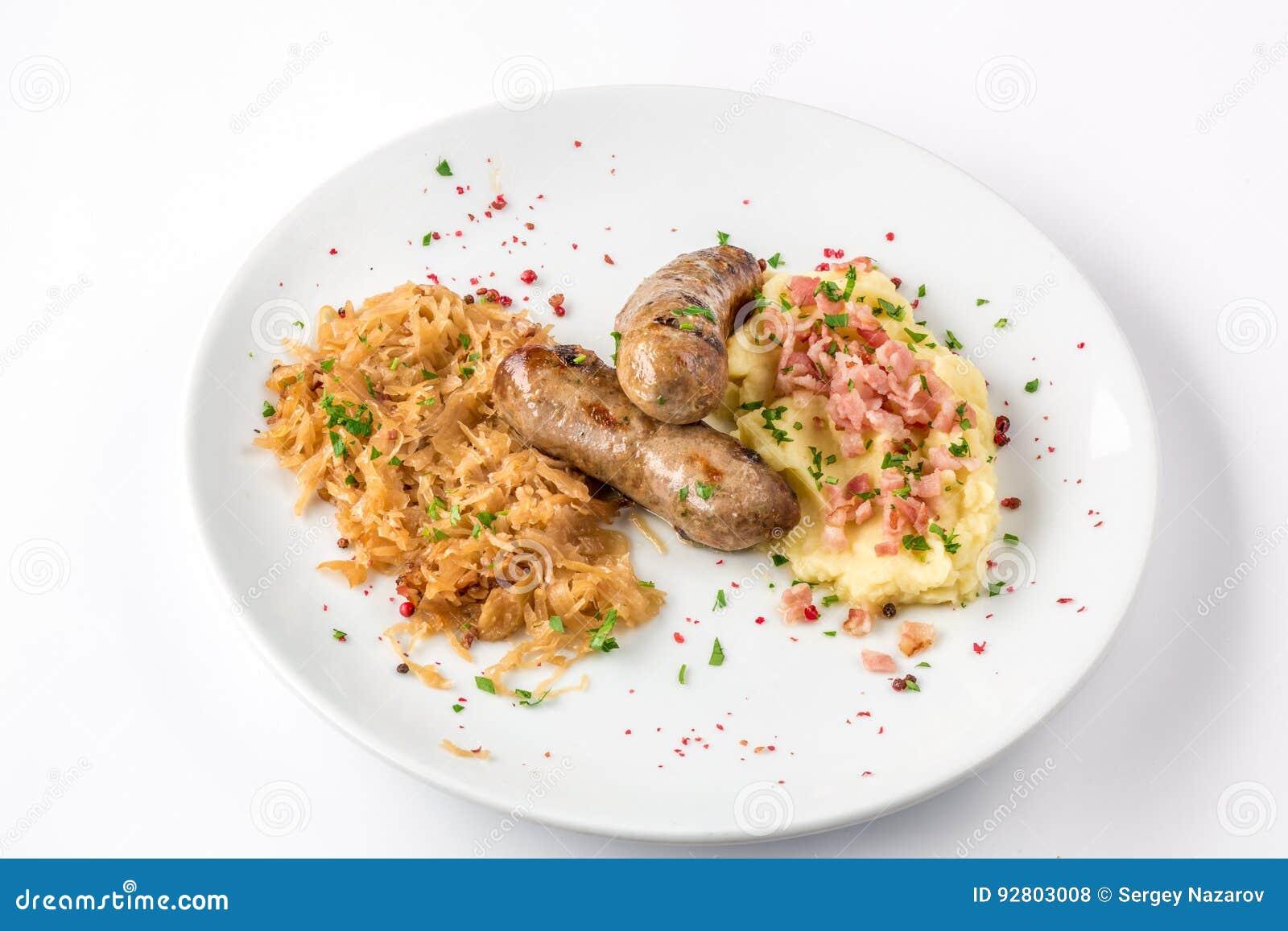 Salsichas grelhadas, batatas e couve assada na opinião branca do close-up da placa de cima de
