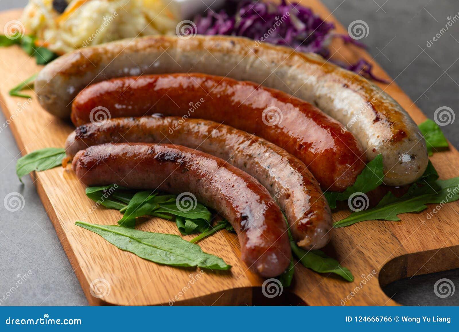 Salsichas grelhadas com as batatas de erva-benta na placa de madeira