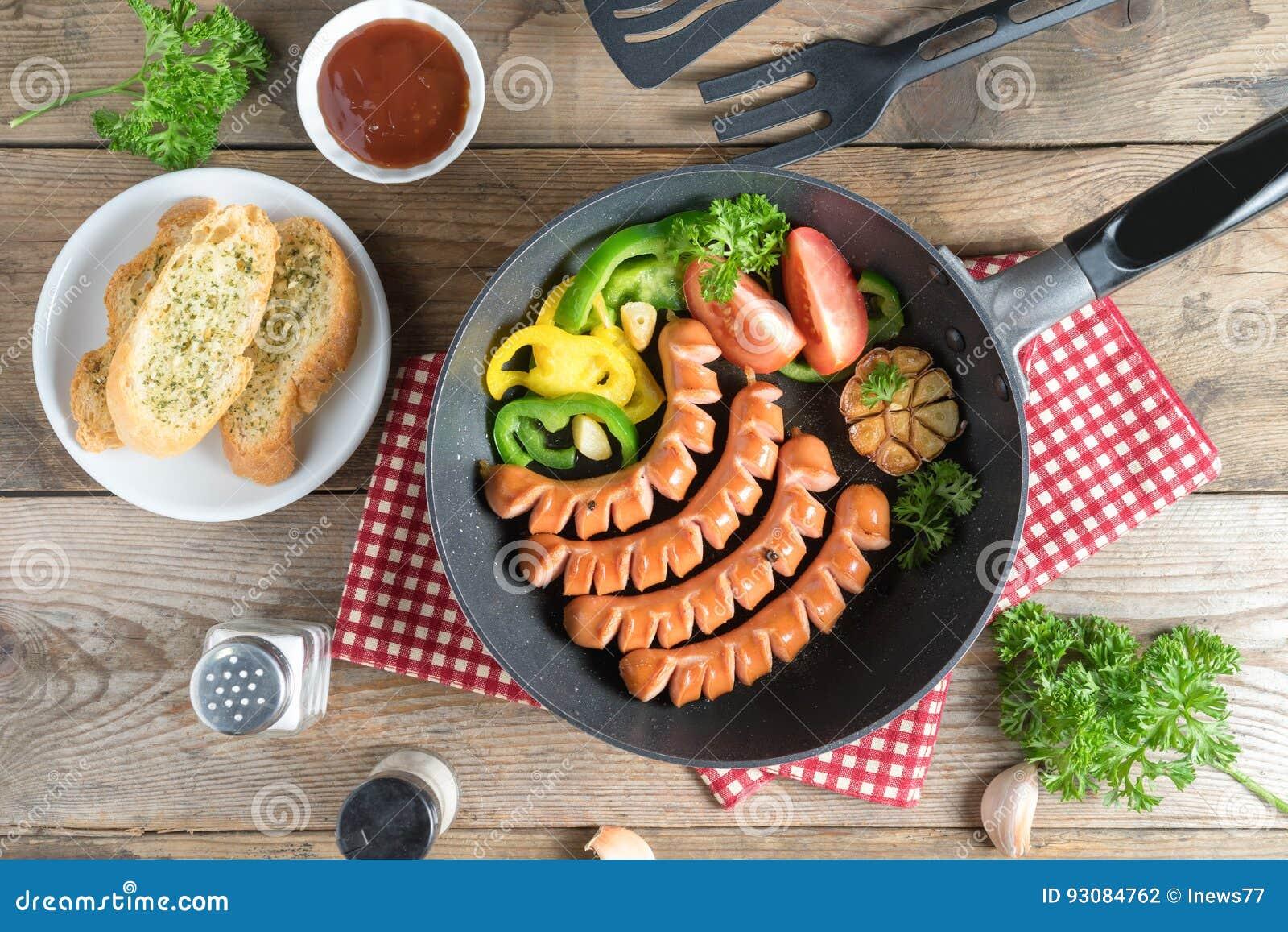 Salsichas grelhadas em uma frigideira