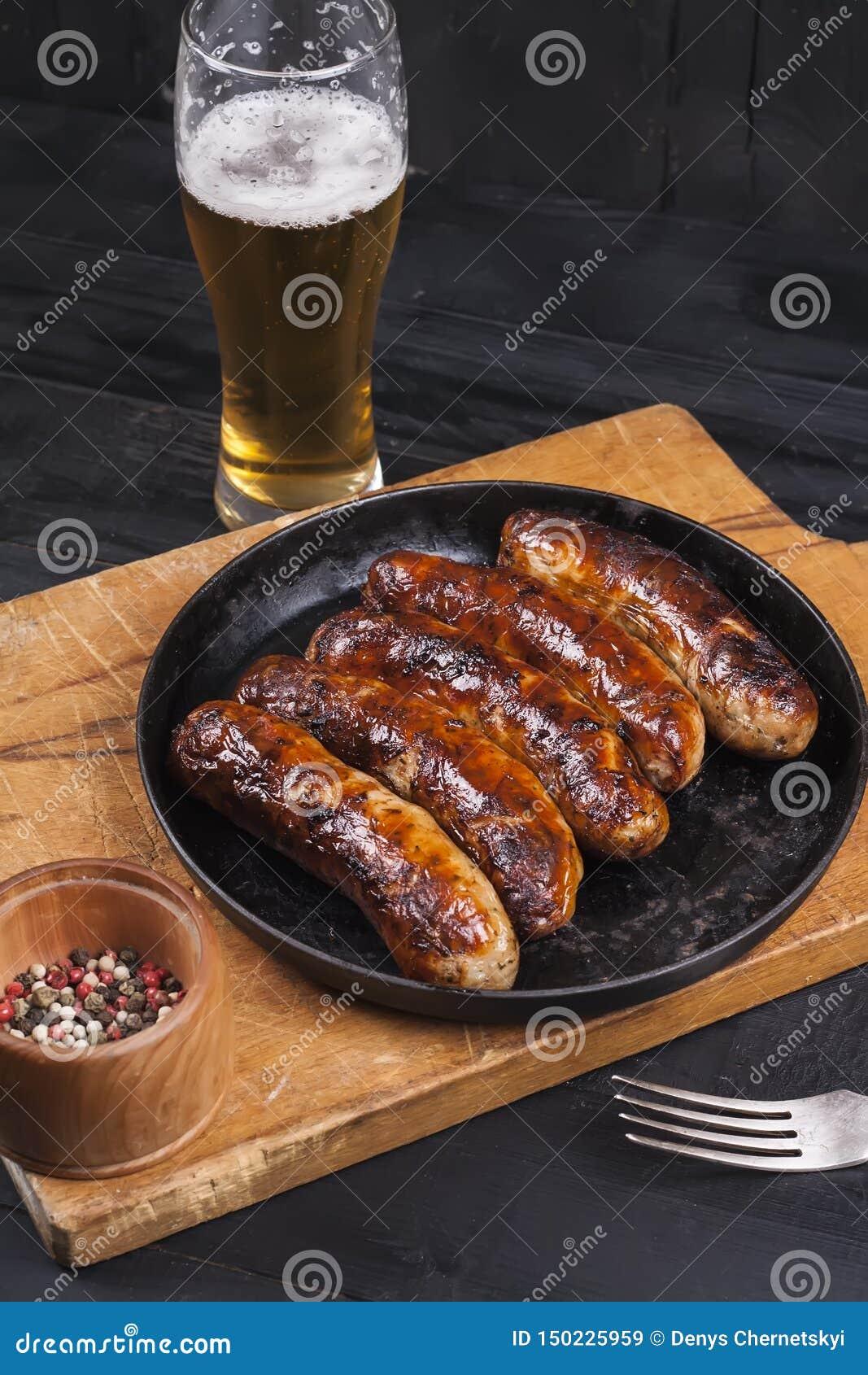 Salsichas grelhadas suculentas da galinha em um fundo de madeira escuro