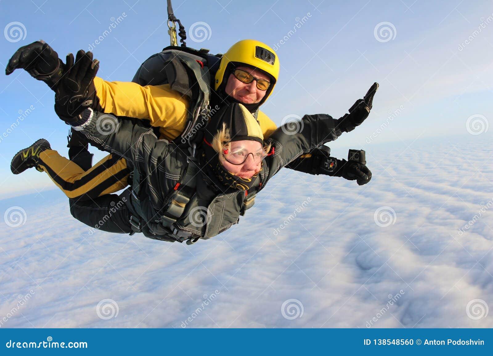 Saltar em queda livre em tandem Os Skydivers estão voando acima das nuvens brancas