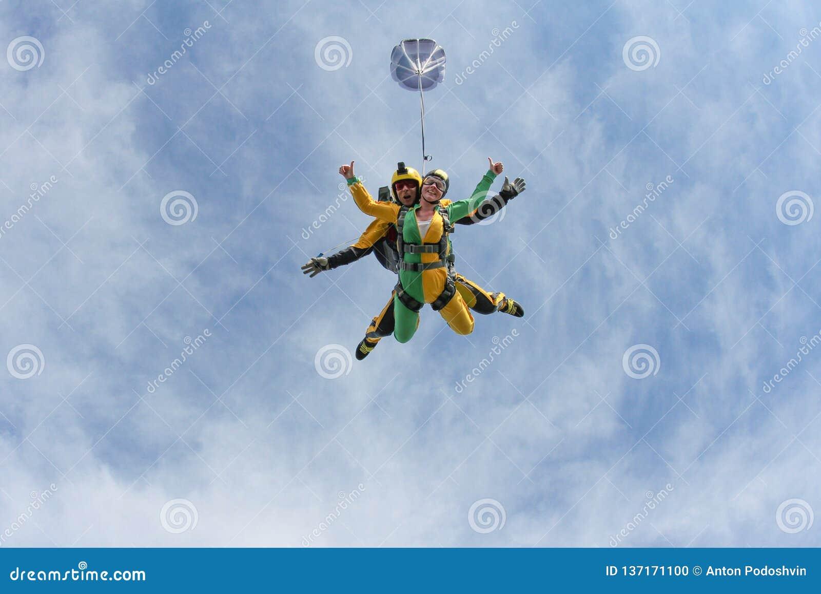 Saltar em queda livre em tandem Uma menina ativa está voando no céu azul