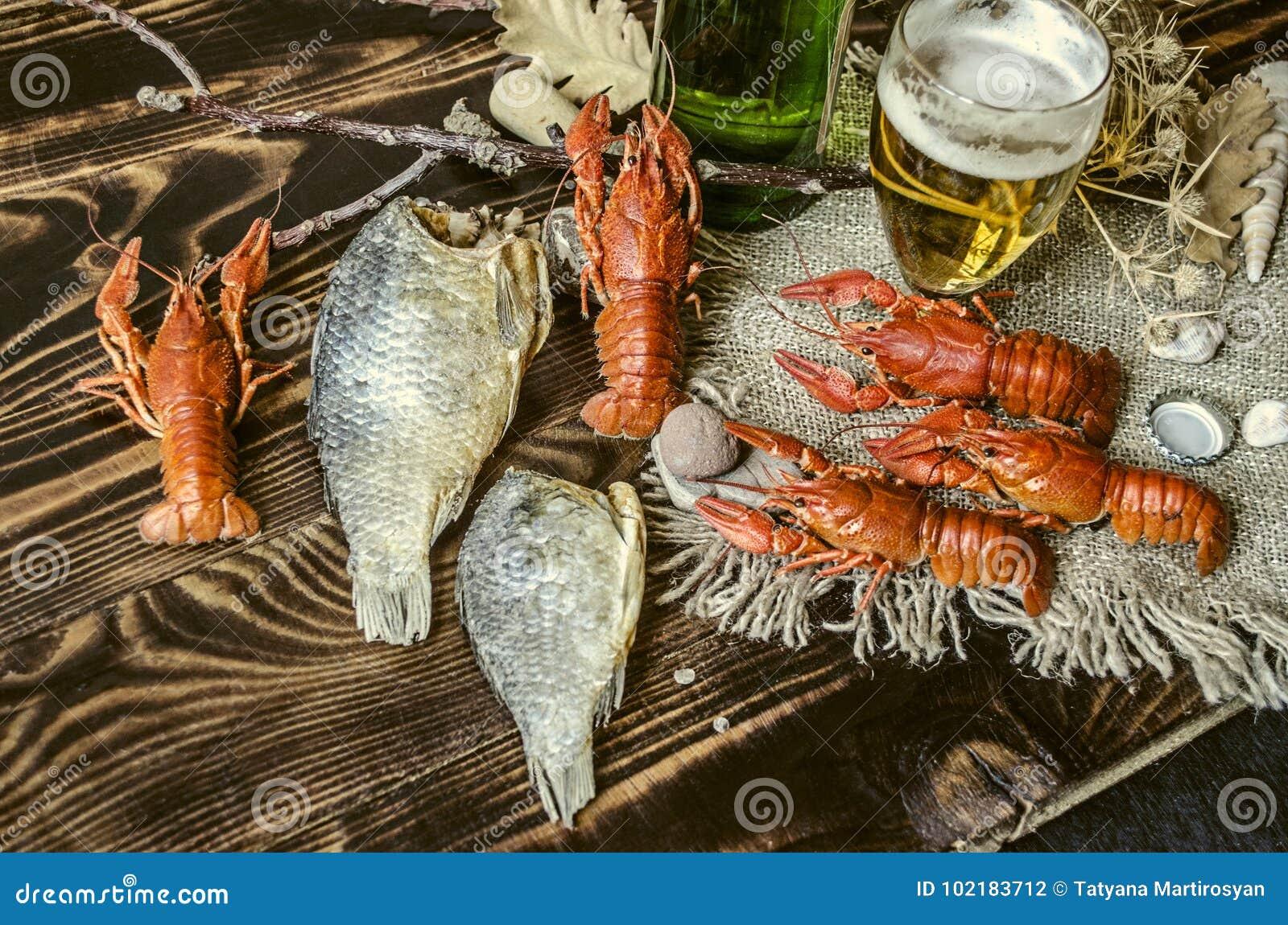 Salted a bouilli les écrevisses rouges avec les poissons salés secs, le verre avec de la bière et une bouteille de bière