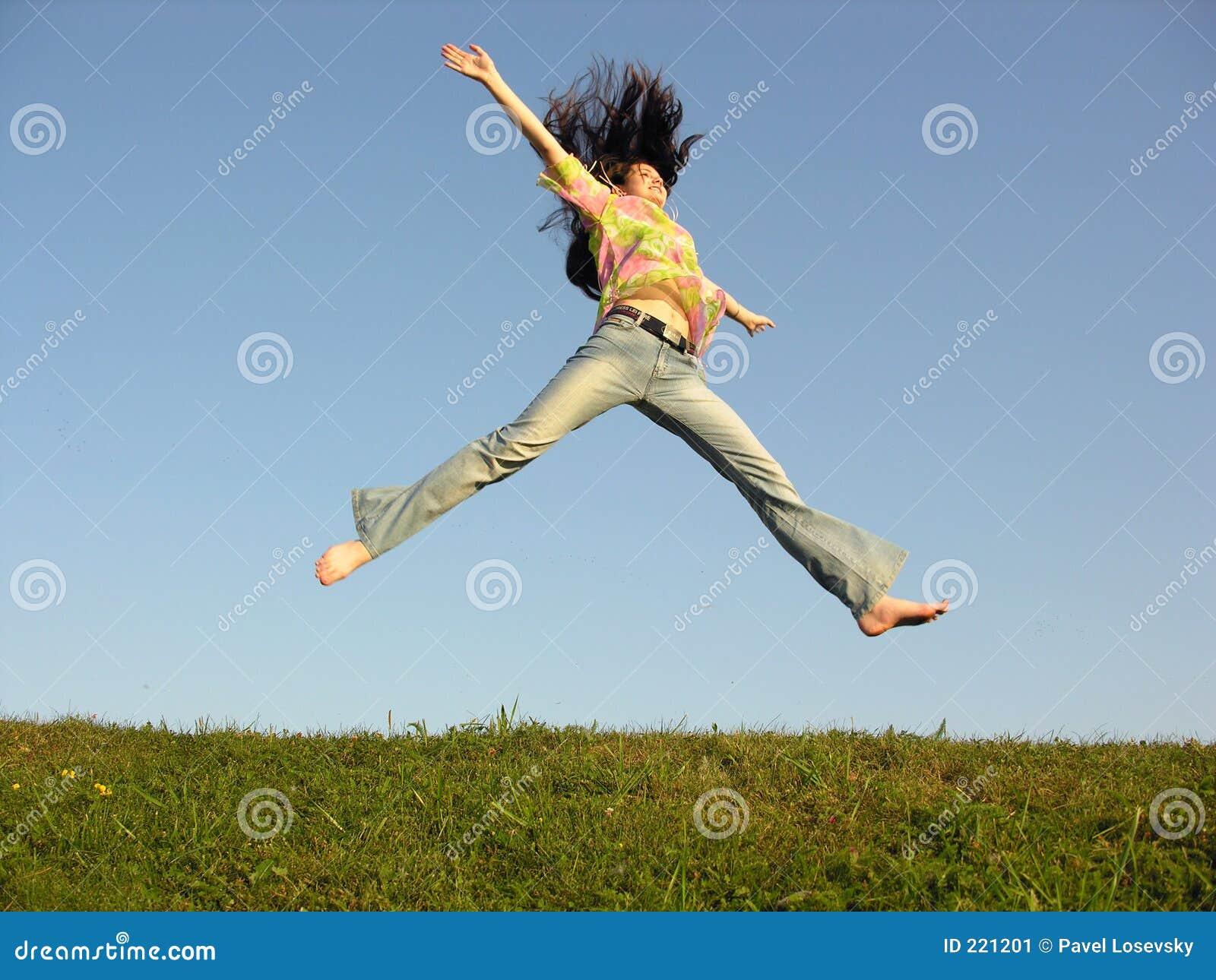 Salti la ragazza con capelli sul cielo