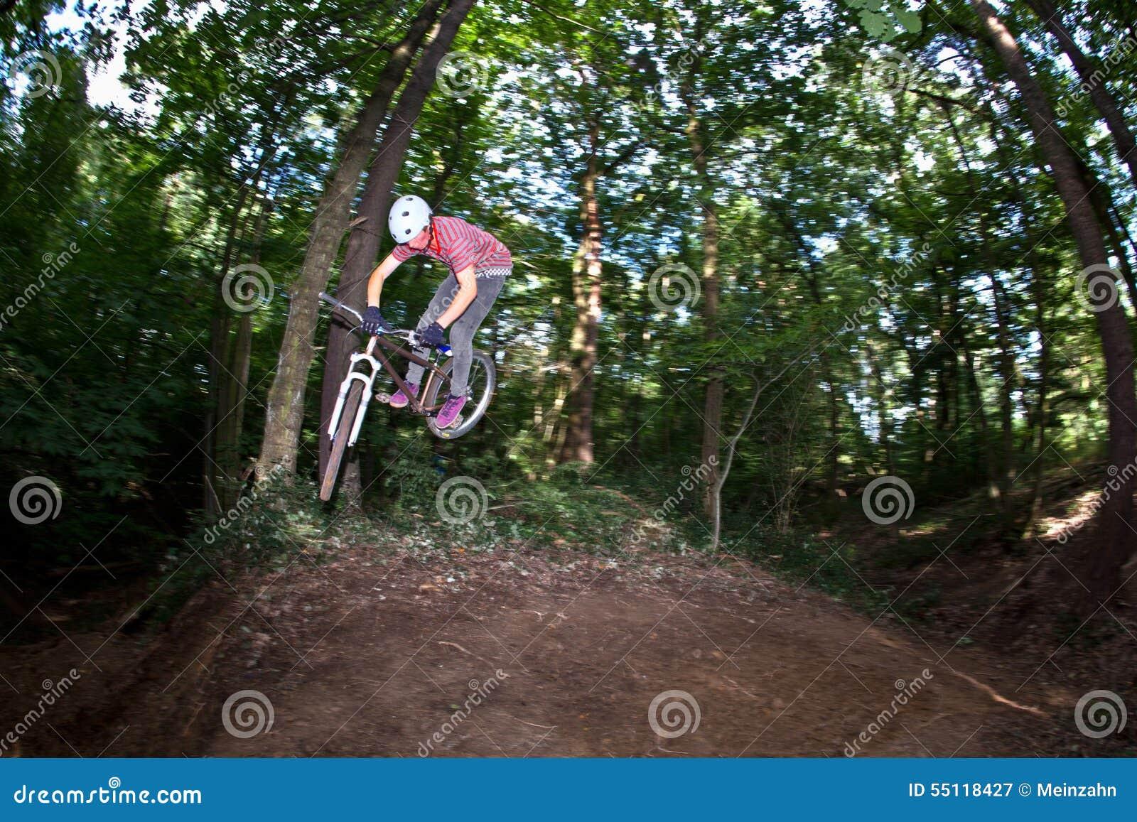 Salto Adolescente Lindo Con Su Bici Sobre Una Rampa Natural En Las ...