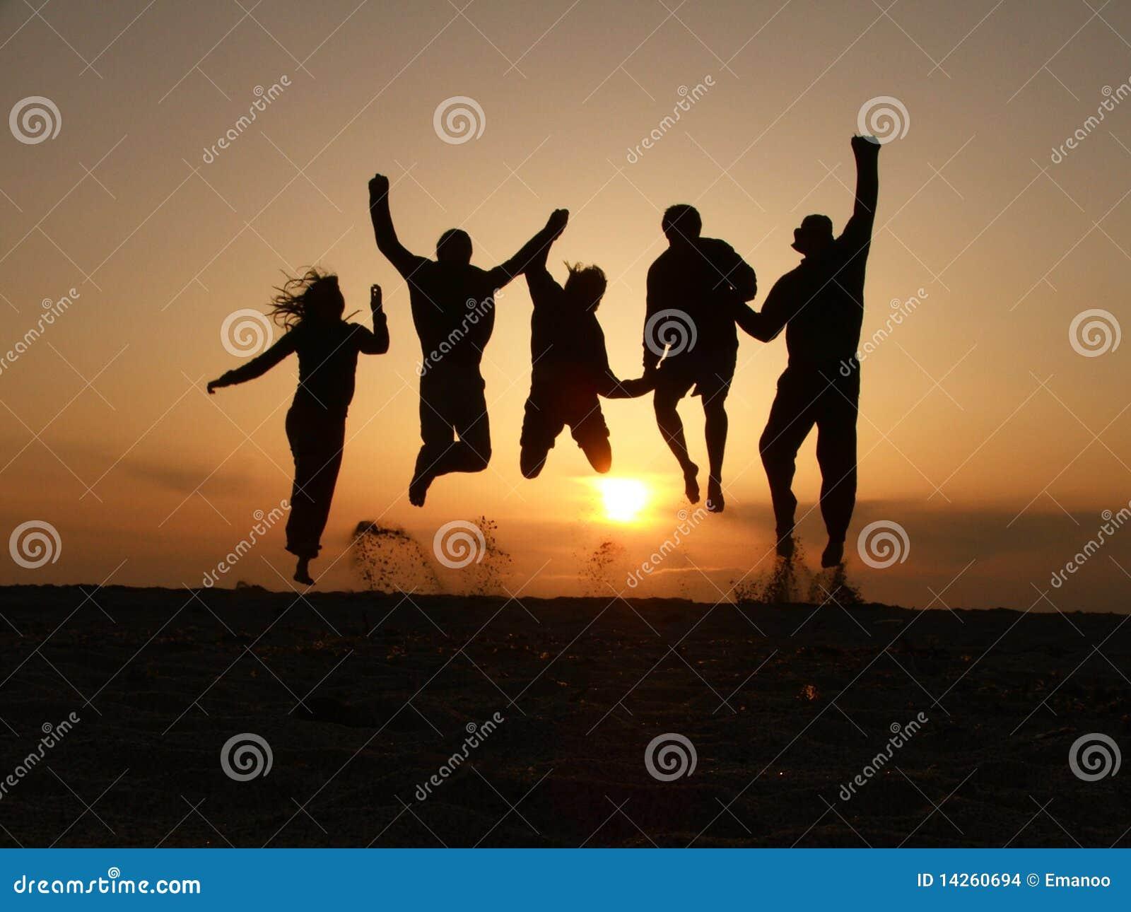 Salto de los amigos de la puesta del sol