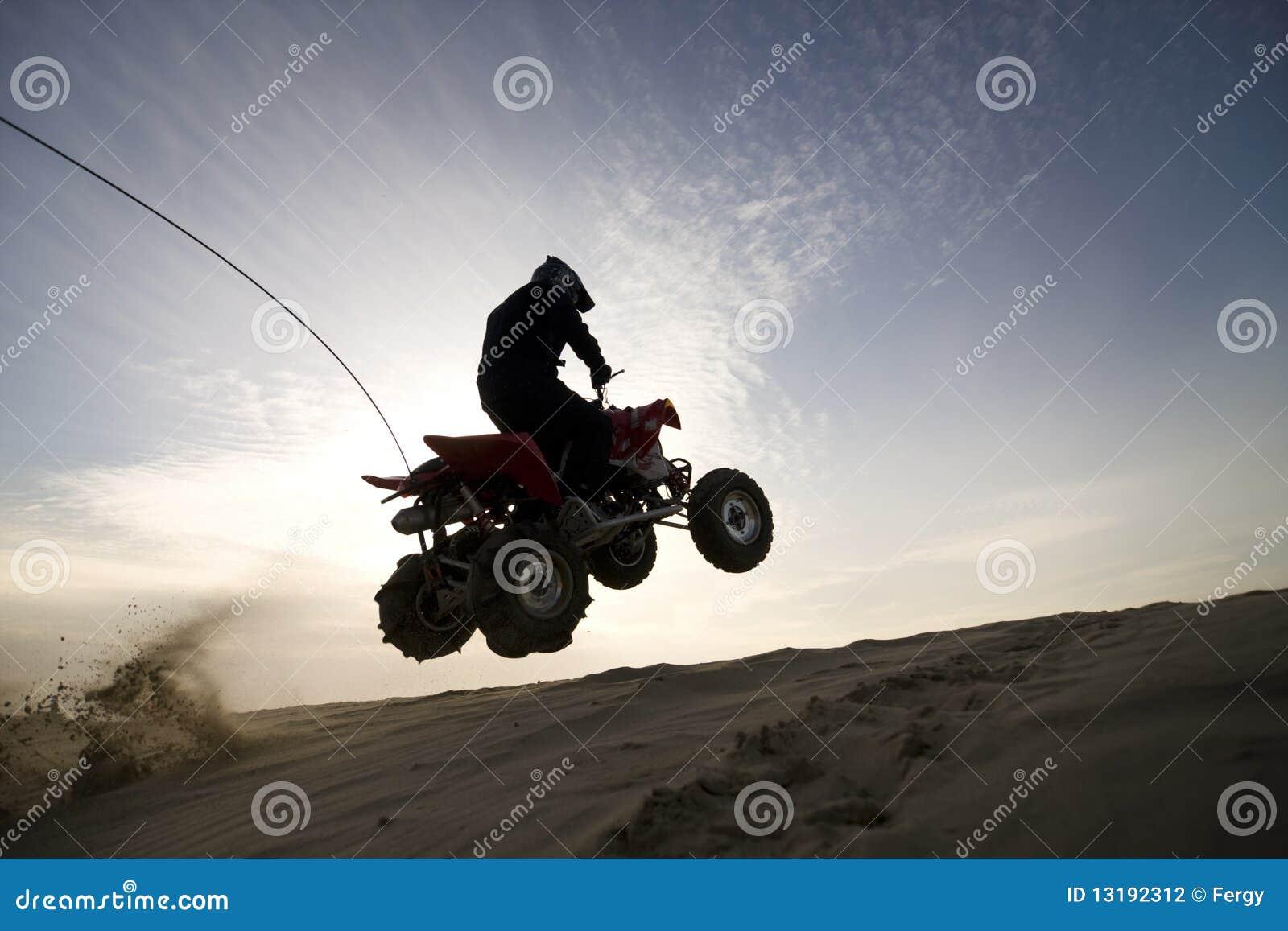Salto do atv da duna no por do sol