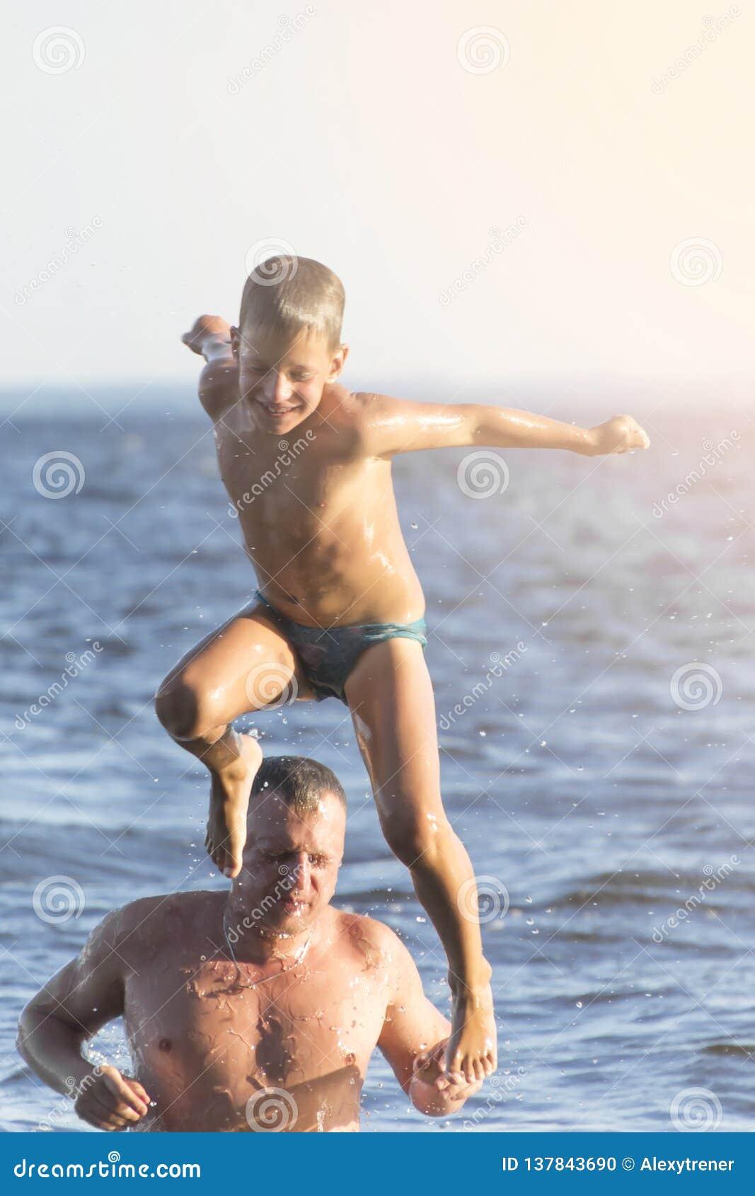 Salto en el agua El hombre y el muchacho se están divirtiendo y están salpicando en el agua Concepto de las vacaciones de verano