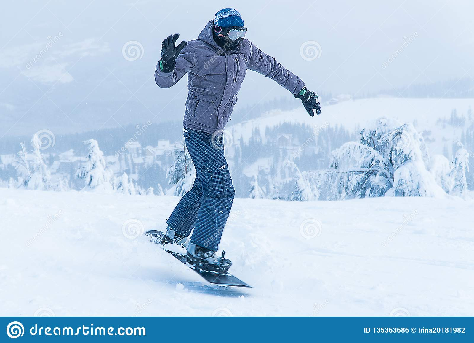 Salto masculino do snowboard da snowboarding vá nas montanhas na snowboarding do inverno da montanha da neve