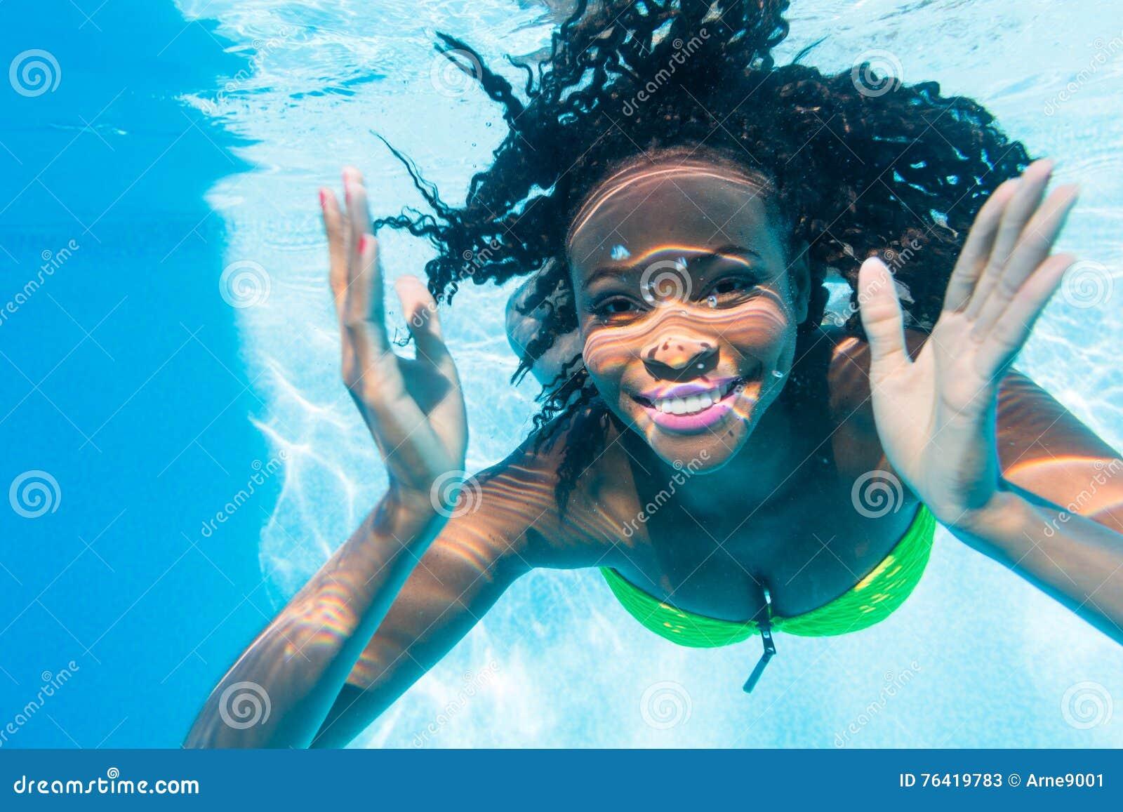 Salto negro de la muchacha en piscina en las vacaciones