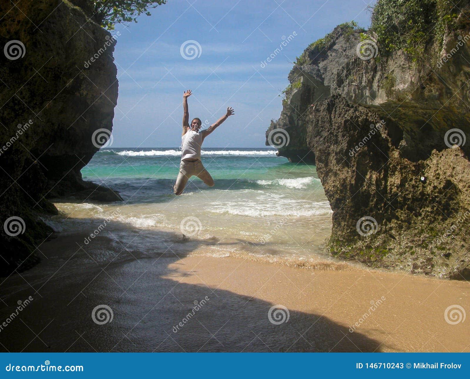 Salto para arriba en una playa ex?tica entre los acantilados que pasan por alto el mar