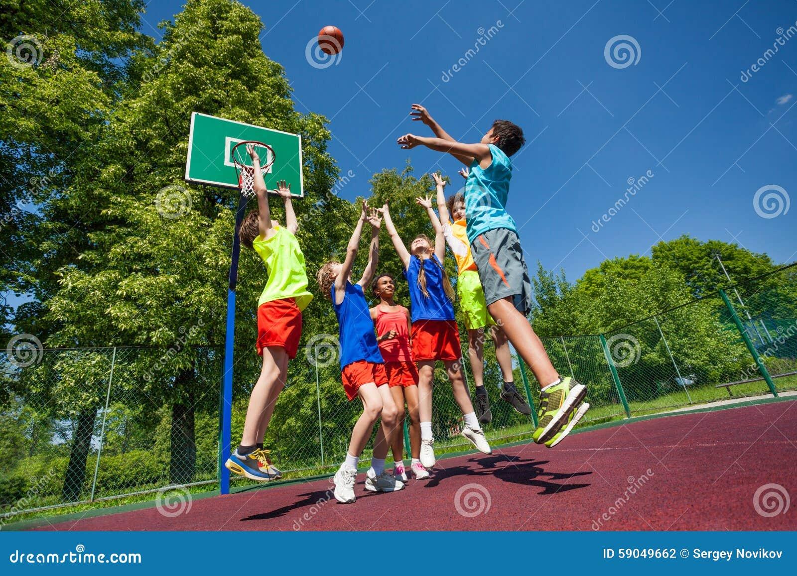 Salto para los adolescentes de la bola que juegan al juego de baloncesto