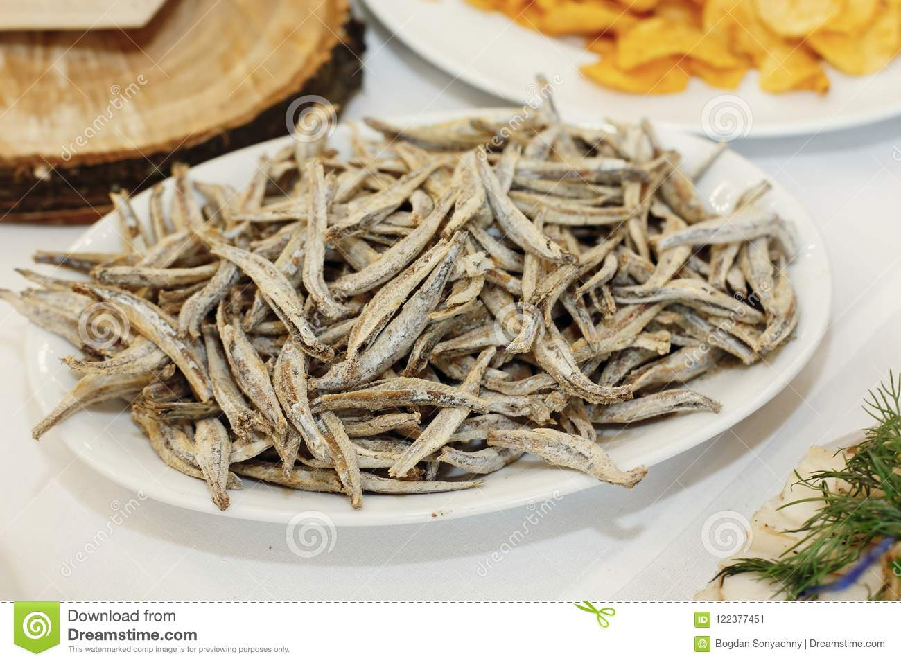 salty smoked anchovies on wooden desk on table, wedding reception. beer bar and snacks. catering in restaurant