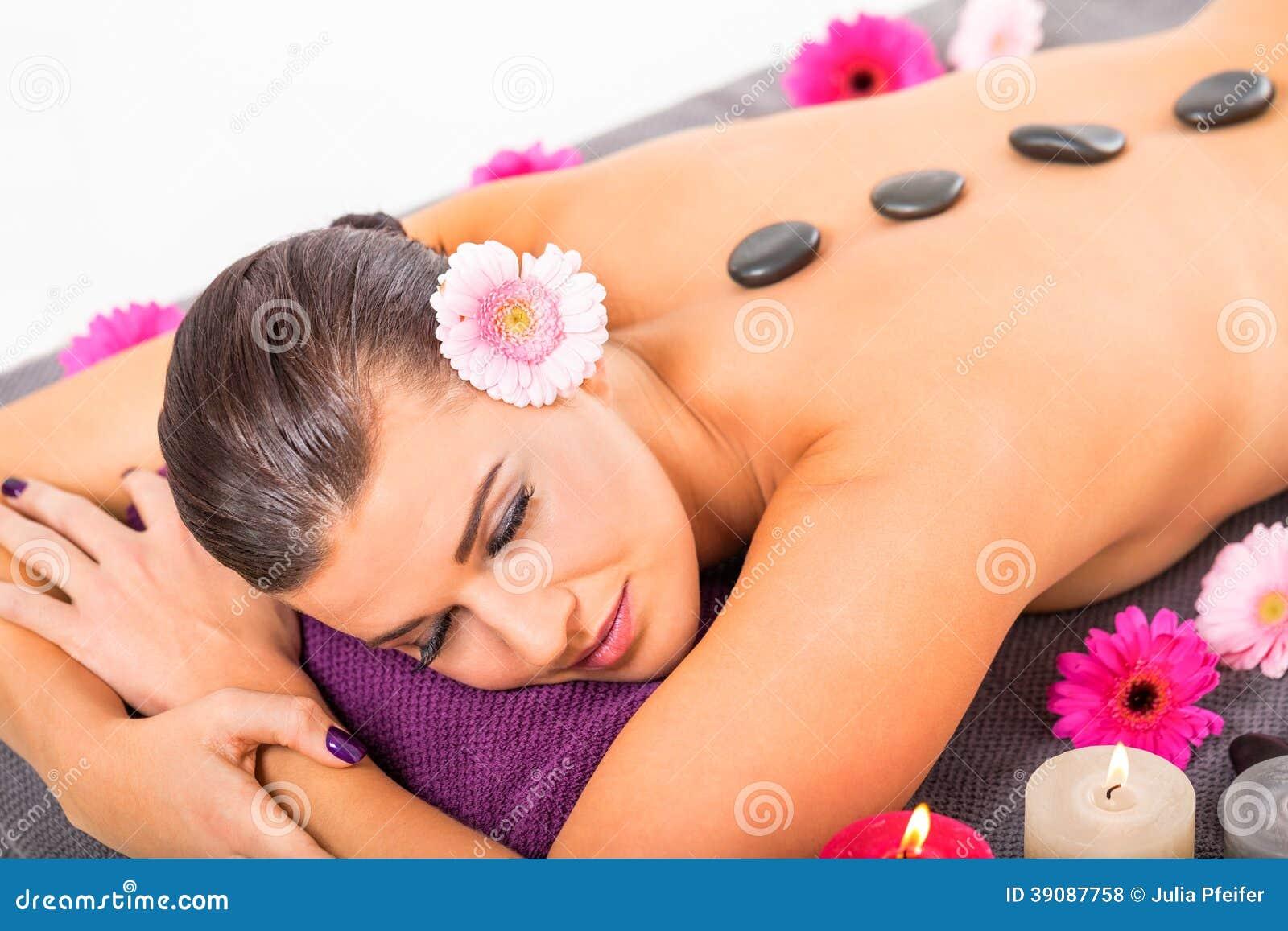 Salud de piedra caliente del masaje de la mujer atractiva joven