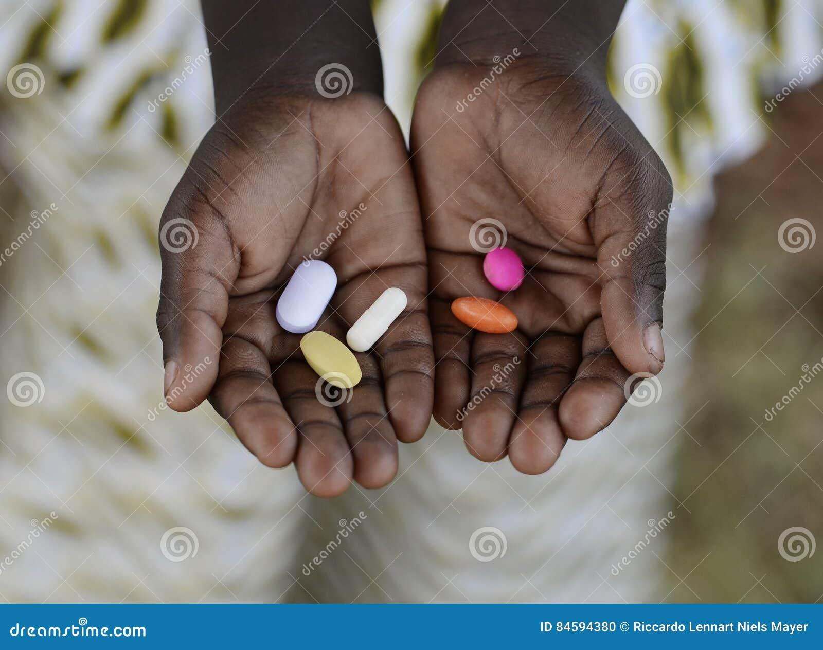 Salud y atención sanitaria: Curando la malaria - muchacha africana que sostiene Pil