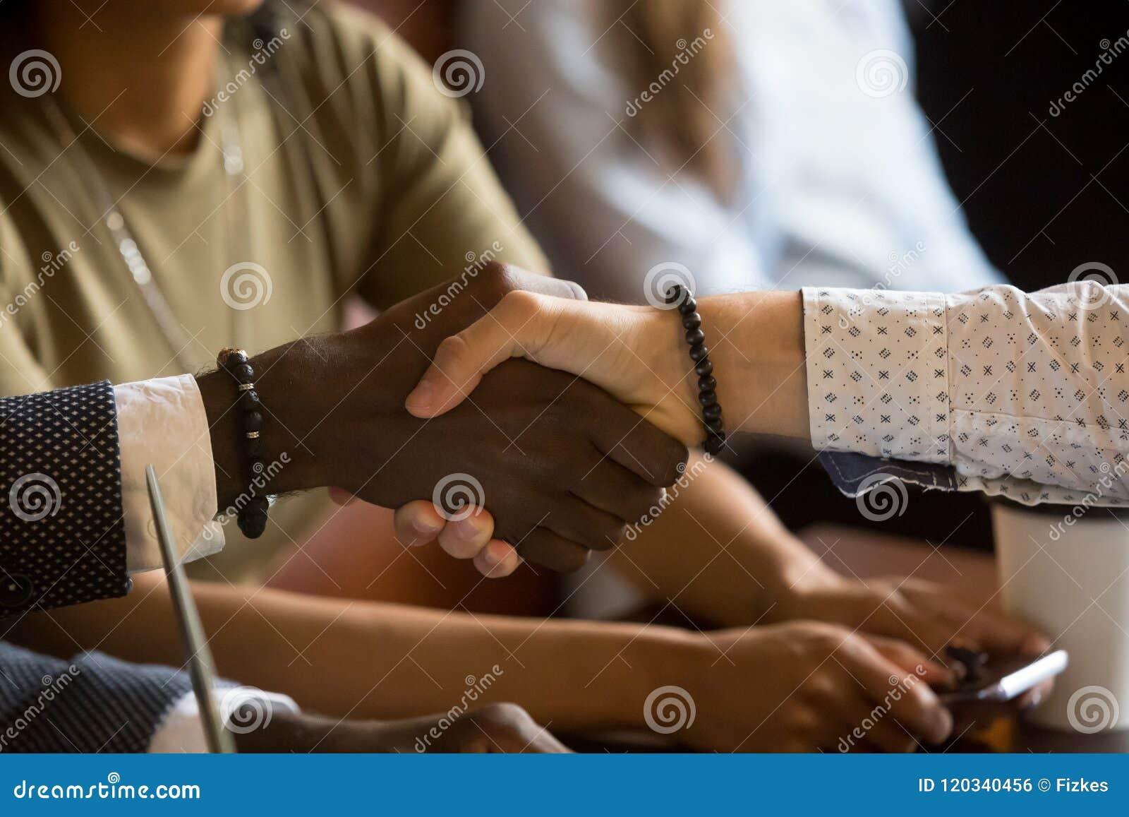 Salutation multiraciale de poignée de main au cours de la réunion d affaires en café