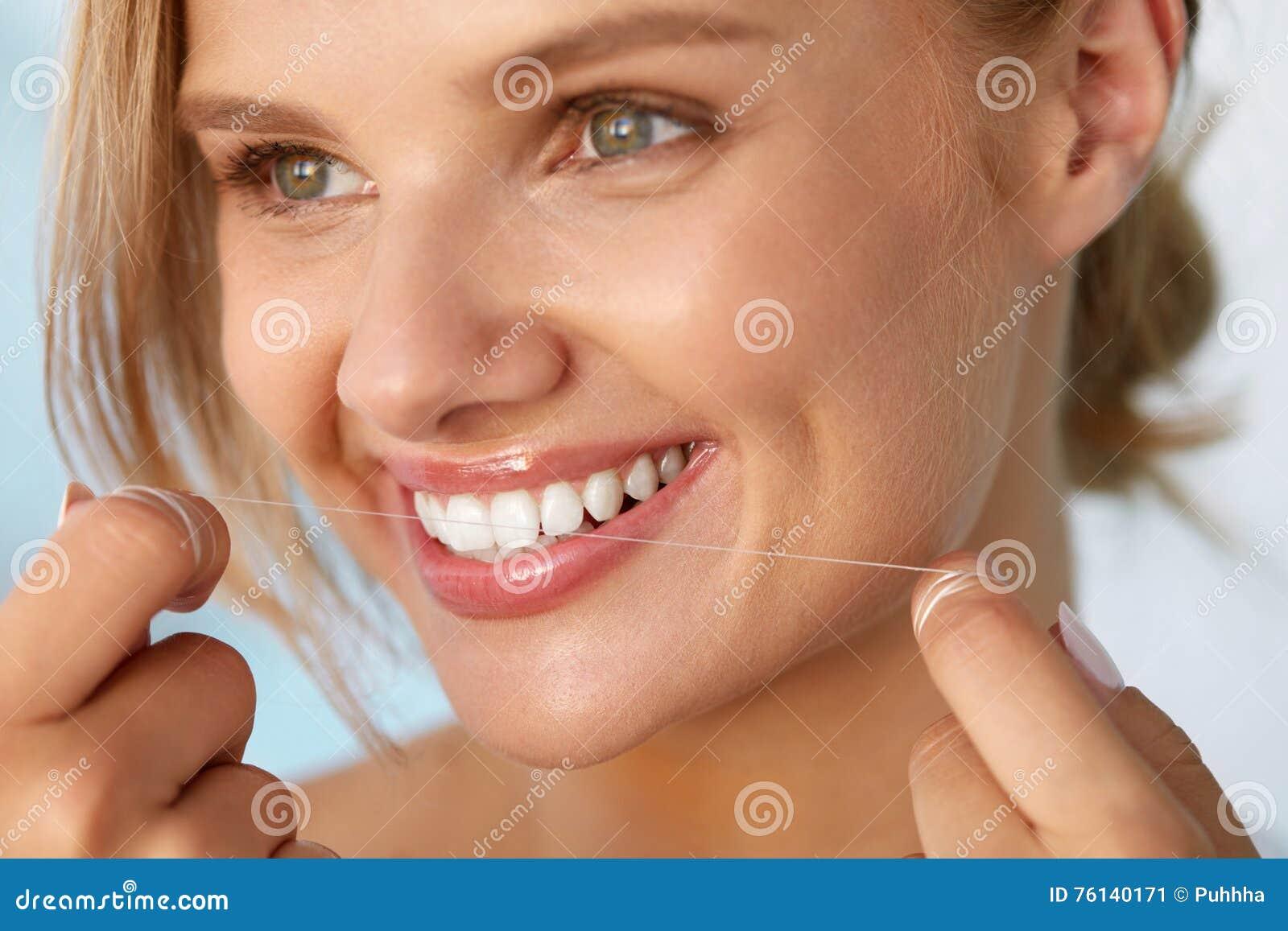 Salute dentale Donna con il bello sorriso che Flossing i denti sani