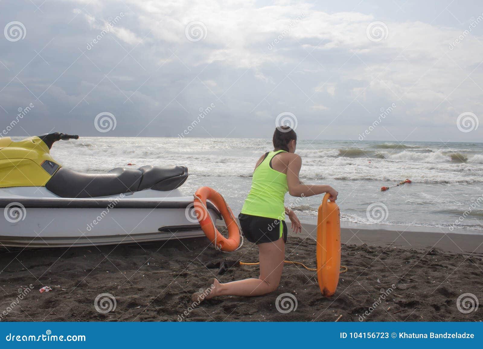 Salva-vidas da menina no dever que mantém uma boia na praia Molhe o  trotinette , ferramenta alaranjada do conservante da equipa