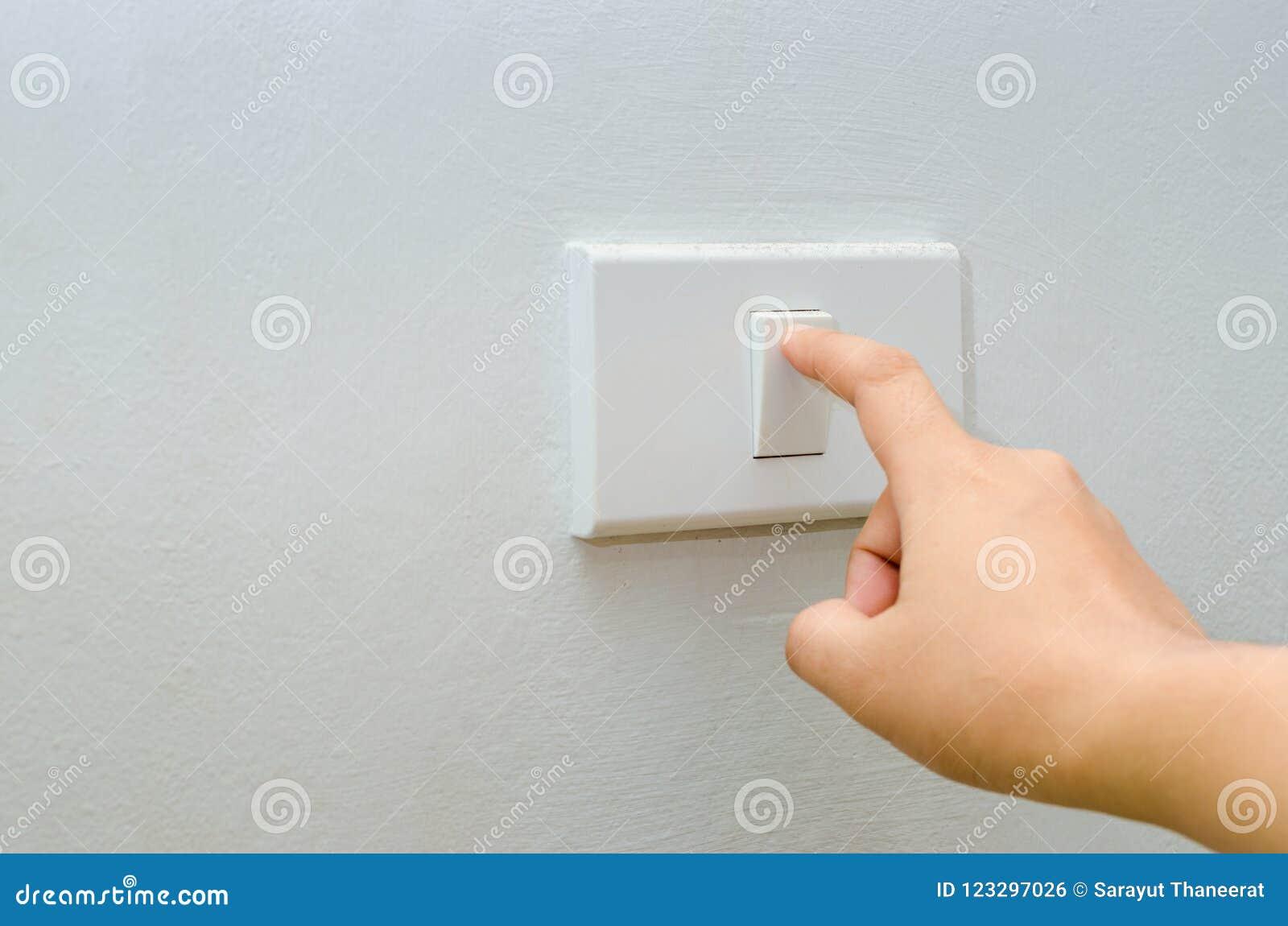 Salvar a eletricidade próxima acima do dedo está girando de ligar/desligar no interruptor da luz mão da mulher com o dedo no espa