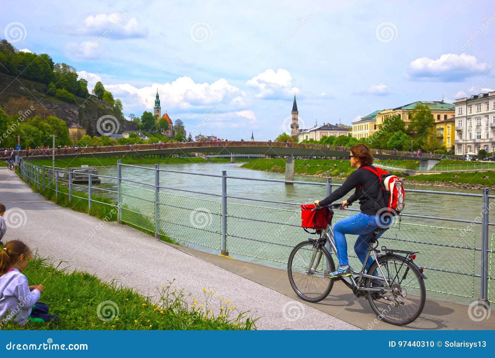 Salzburg, Austria - May 01, 2017: Cyclist on the embankment in Salzburg