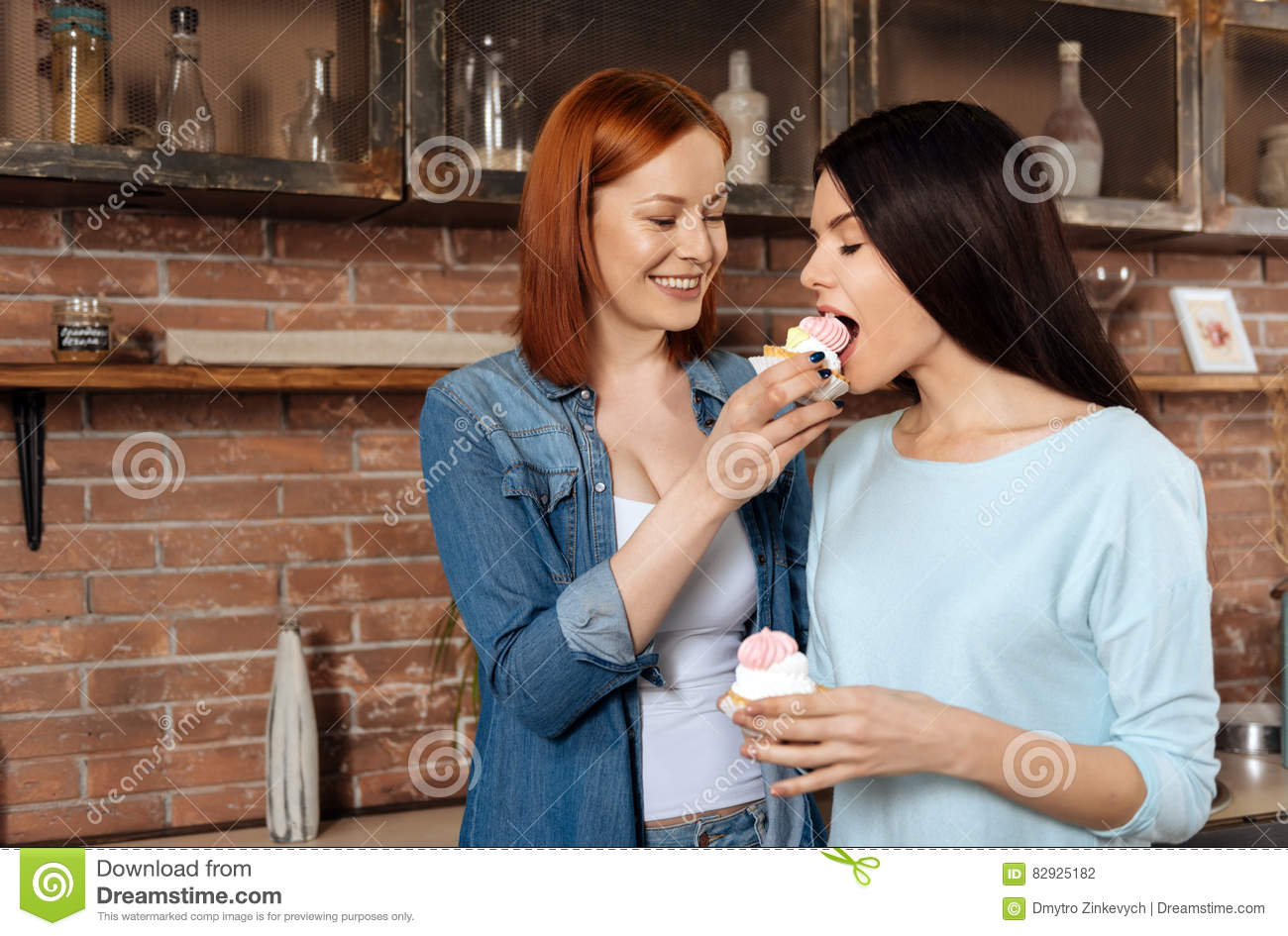 Red haired women wearing casual clothes feeding her girlfriend with dessert  that keeping her eyes closed