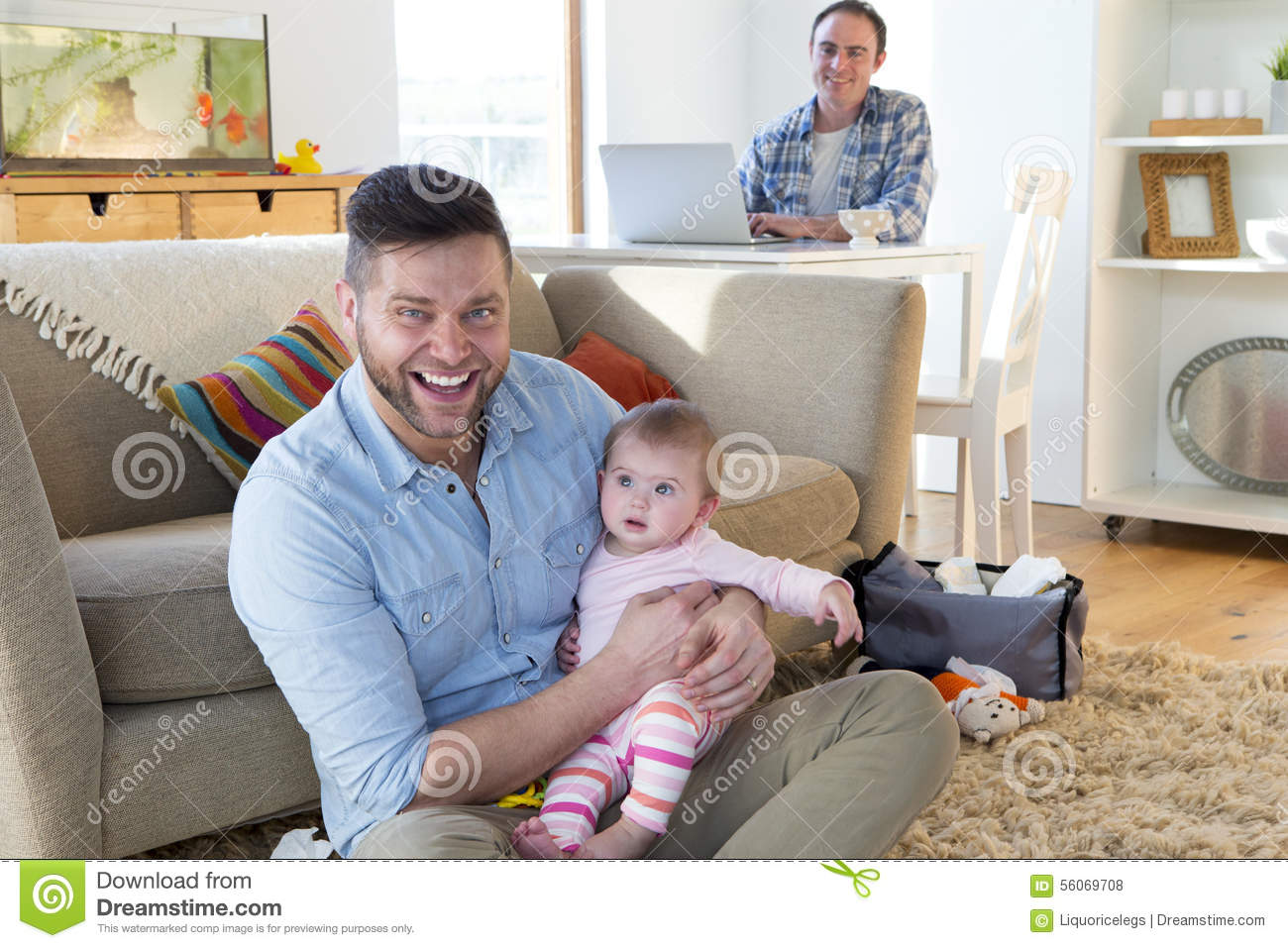 Same sex male couple sitting in their home. One father is sitting on the  floor with their daughter in his arms. They are both smiling at the camera.