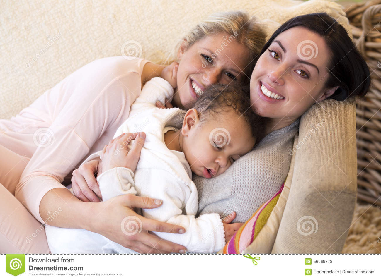 Same sex couple snuggling with their baby son