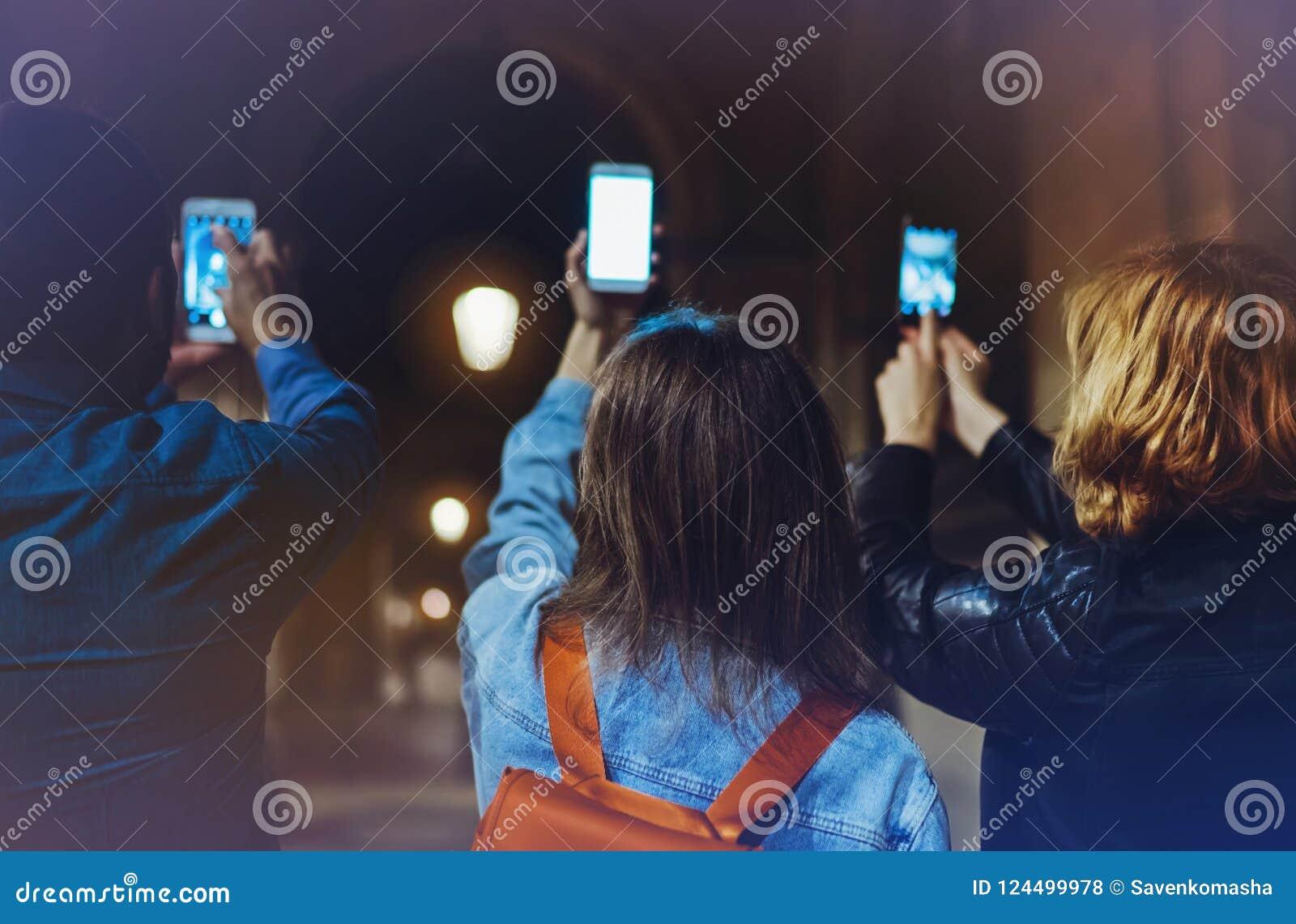 Samen richten groeps volwassen hipsters die in handen mobiele telefoonclose-up, het online concept van WiFi Internet in straat, b
