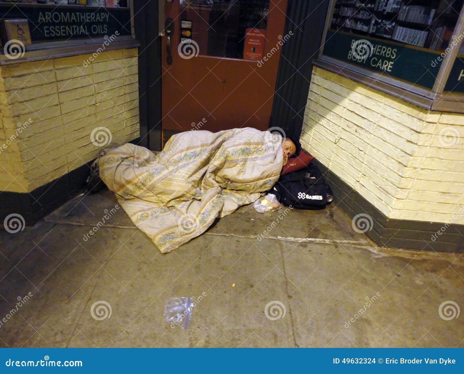 Samengebundelde dakloze persoonsslaap op deurmanier van opslag onder bl