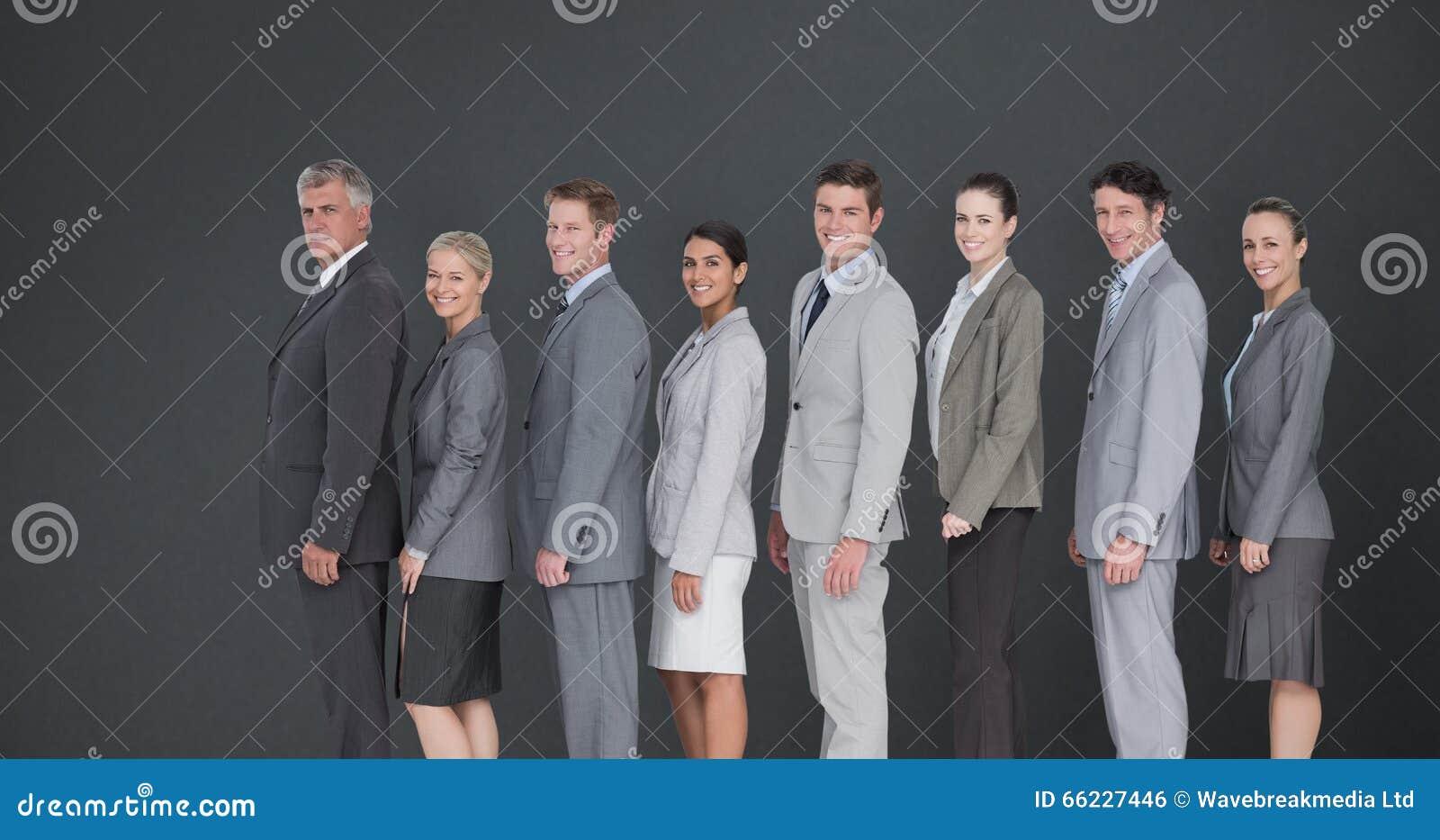 Samengesteld beeld die van commercieel team zich in rij bevinden en bij camera glimlachen