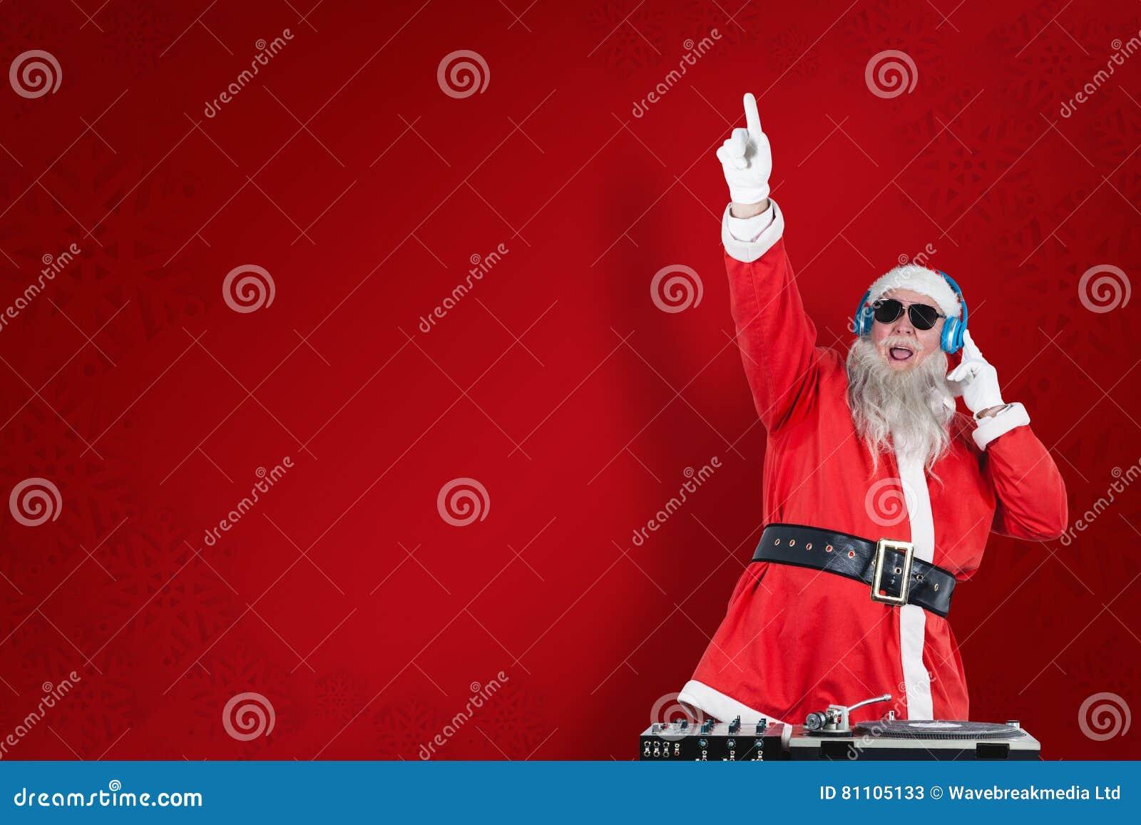 Samengesteld beeld die van de Kerstman DJ met opgeheven hand spelen