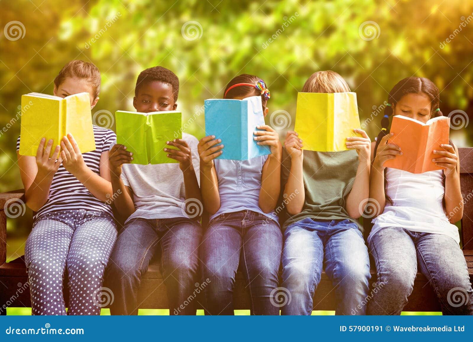 Samengesteld beeld van kinderen die boeken lezen bij park