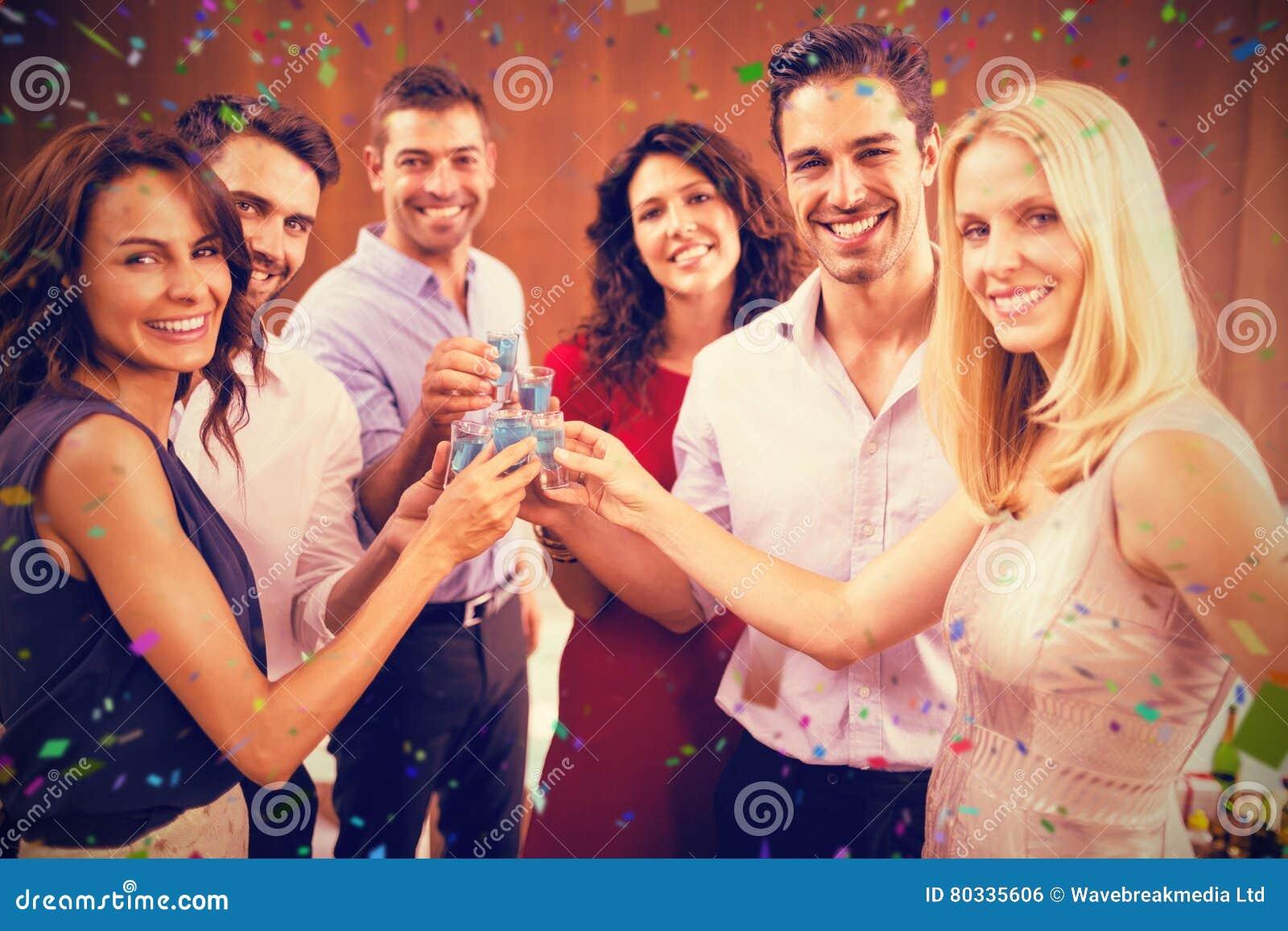 Samengesteld beeld van portret van vrienden die schoten drinken terwijl zich het verenigen
