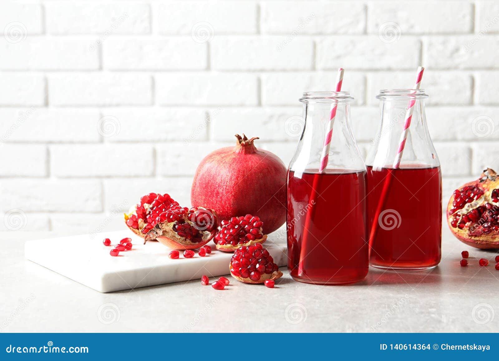 Samenstelling met flessen vers granaatappelsap op lijst