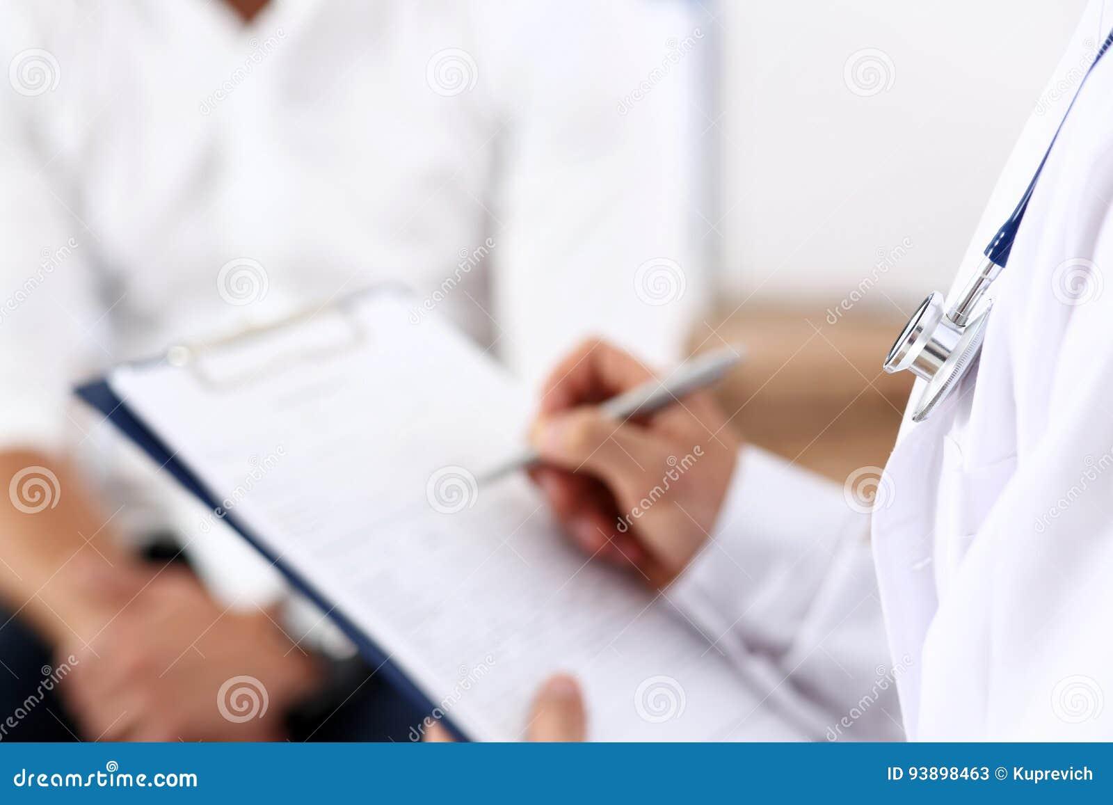 Samiec lekarki ręki chwyta srebra pióro wypełnia cierpliwej historii listę