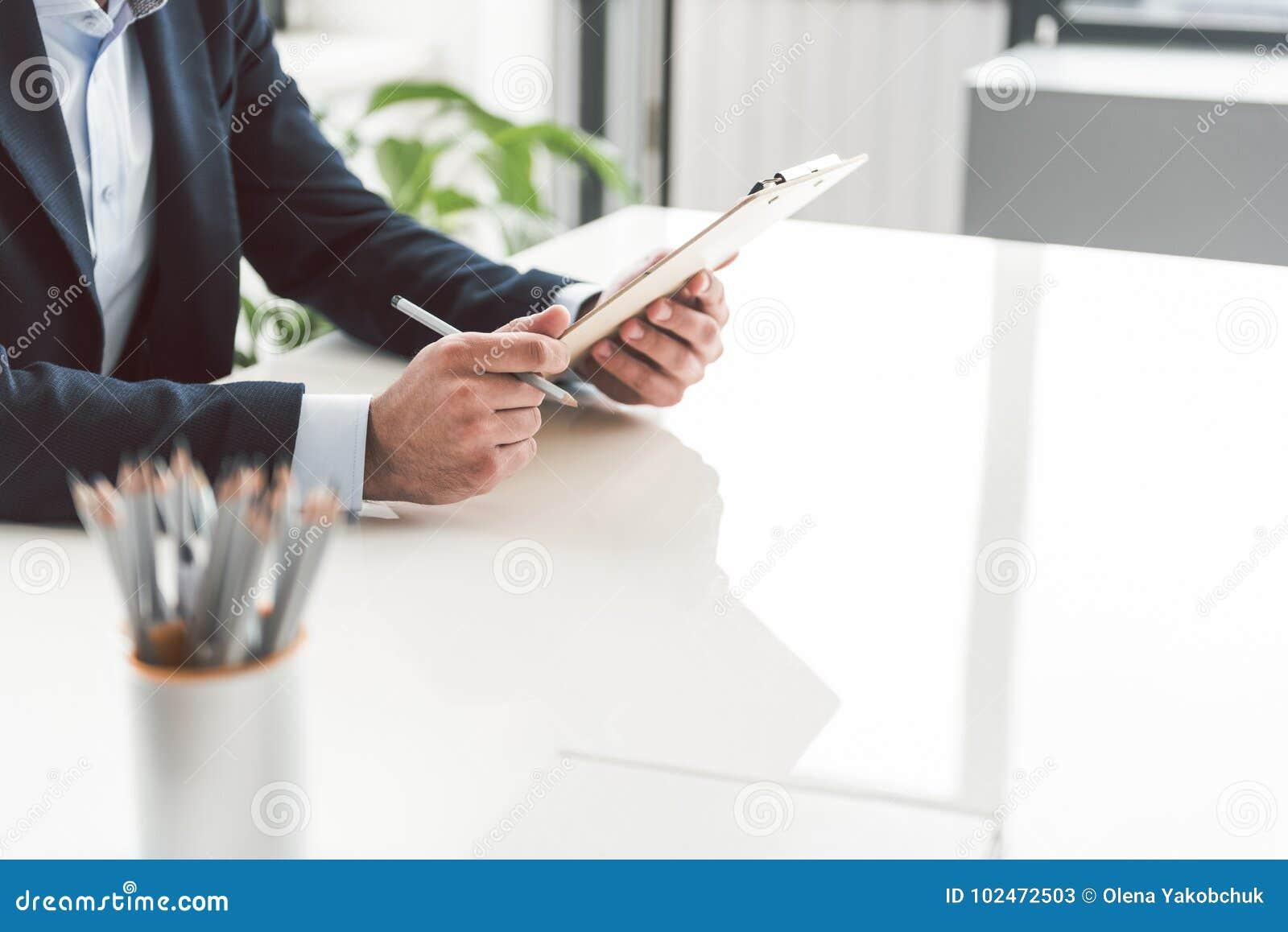 Samiec ręki utrzymuje schowek przy biurkiem