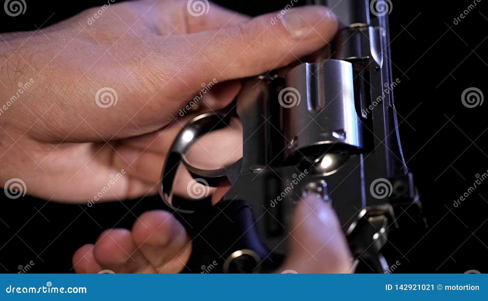 Samiec wręcza mieniu stalowego rewolwerowego zbliżenie, zabójcy narządzania broń, ochrona
