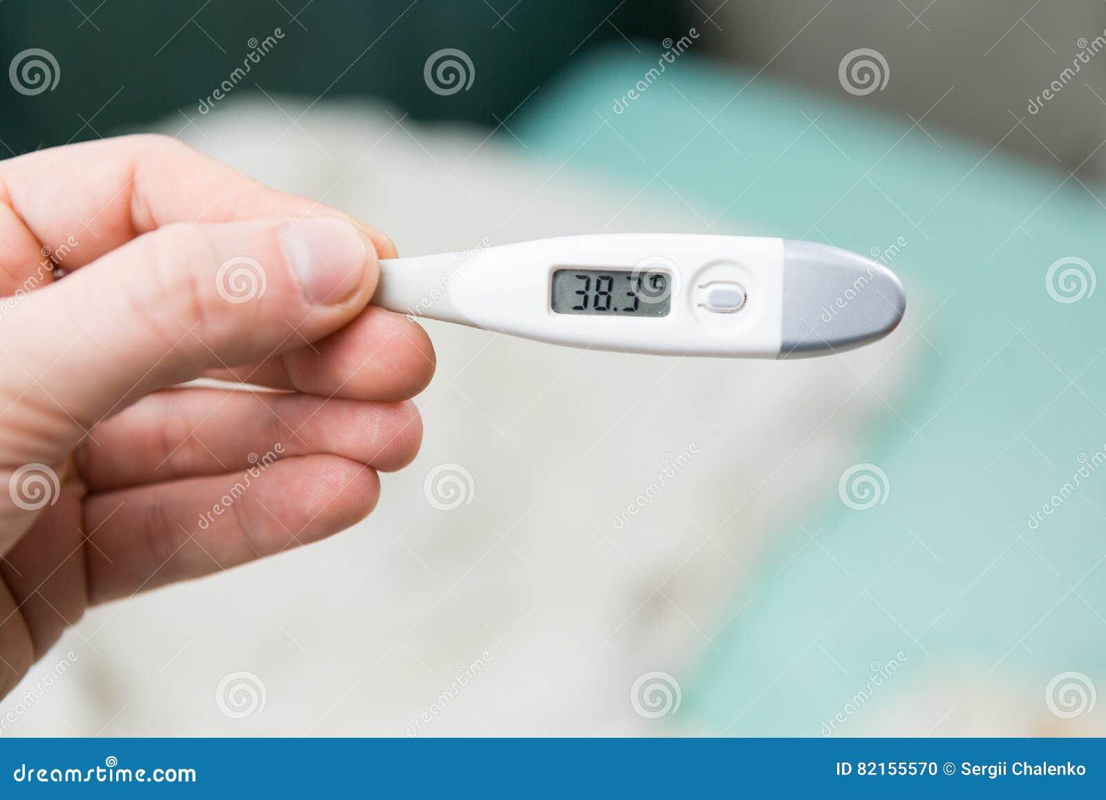 Samiec wręcza trzymać cyfrowego termometr