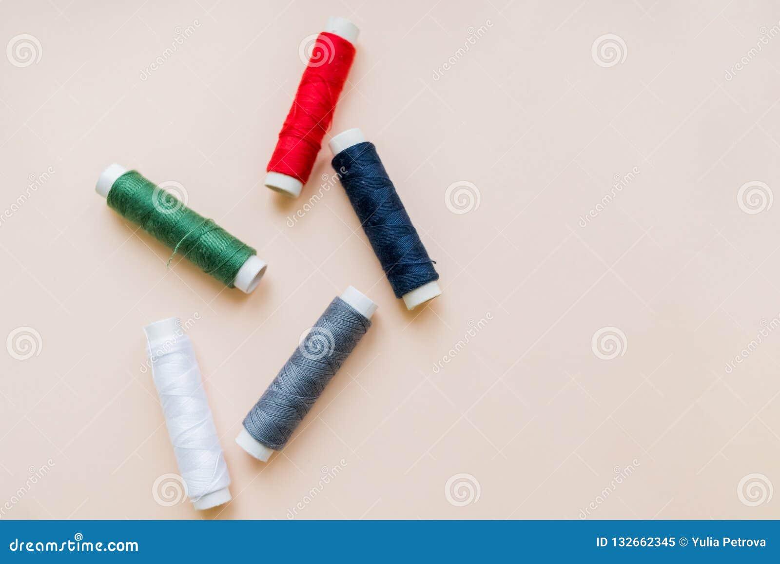 Samling av olika sy trådar på pastellfärgad bakgrund Varje skjutas separat knittinnghjälpmedel naturlig bomull