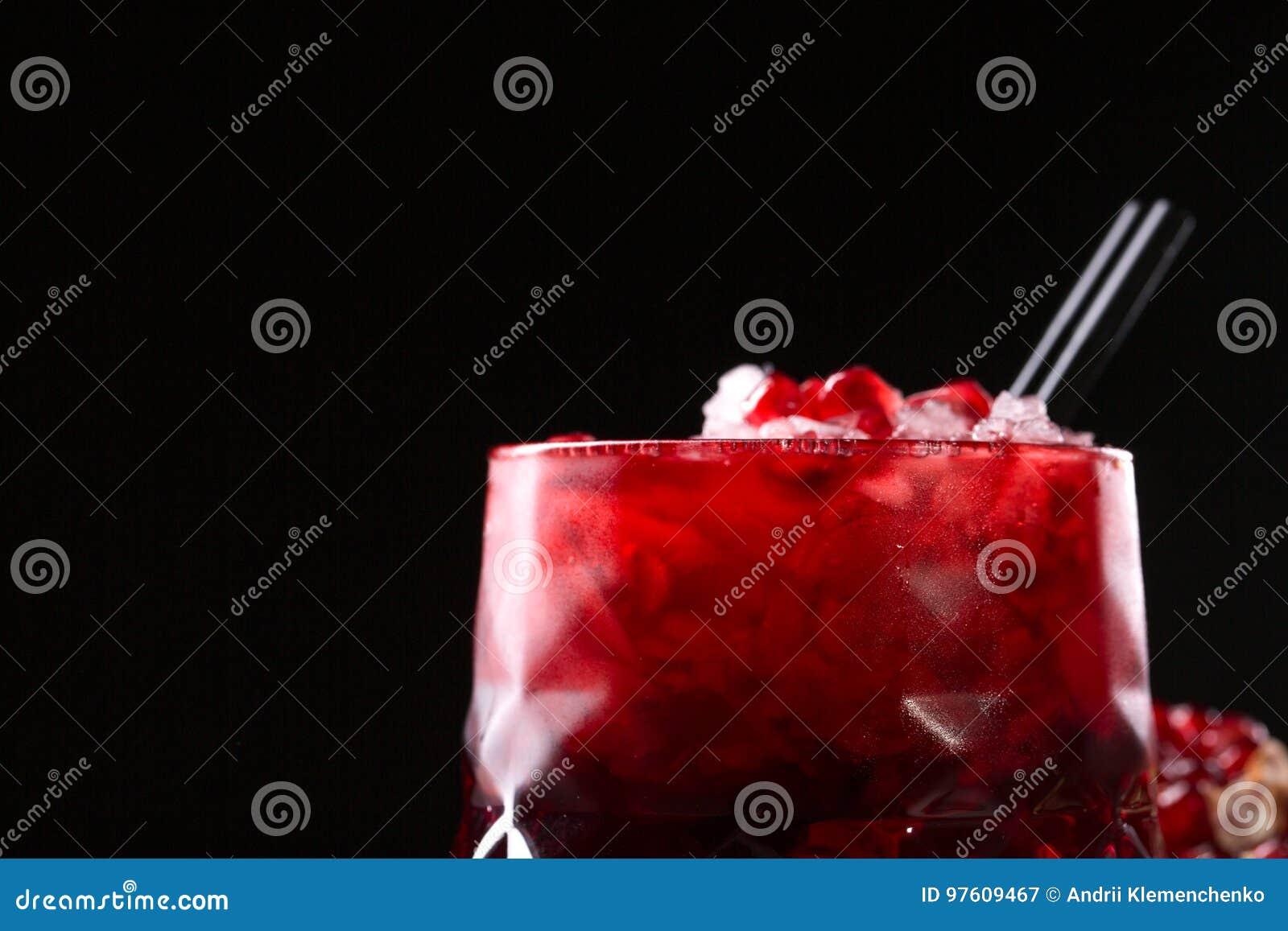 Sammanpressad granatäpplefruktsaft med krossad is och svarta sugrör på en svart bakgrund Organisk och fördelgranatröttdryck