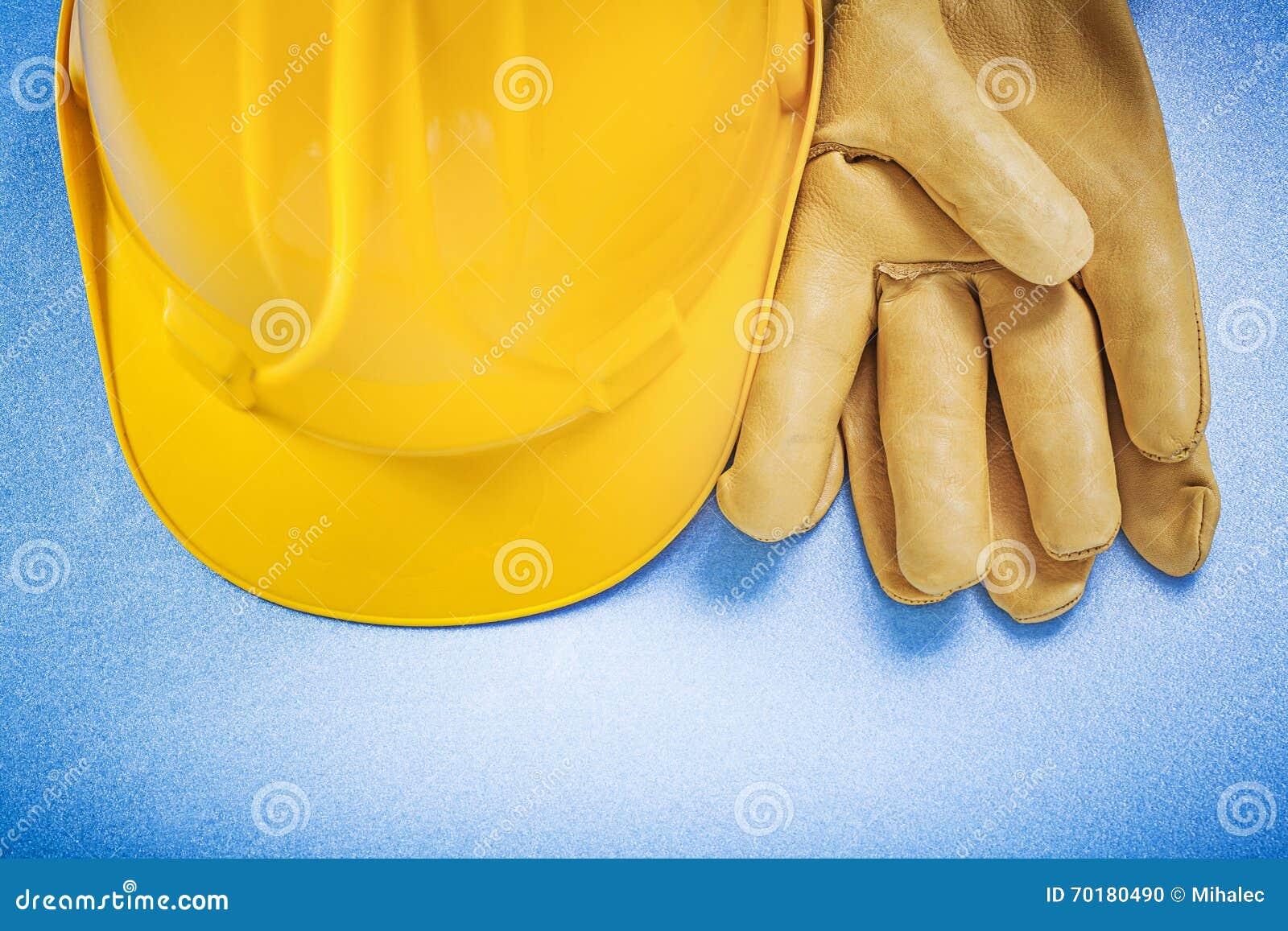 Sammansättning av för lädersäkerhet för hård hatt handskar på blå bakgrund