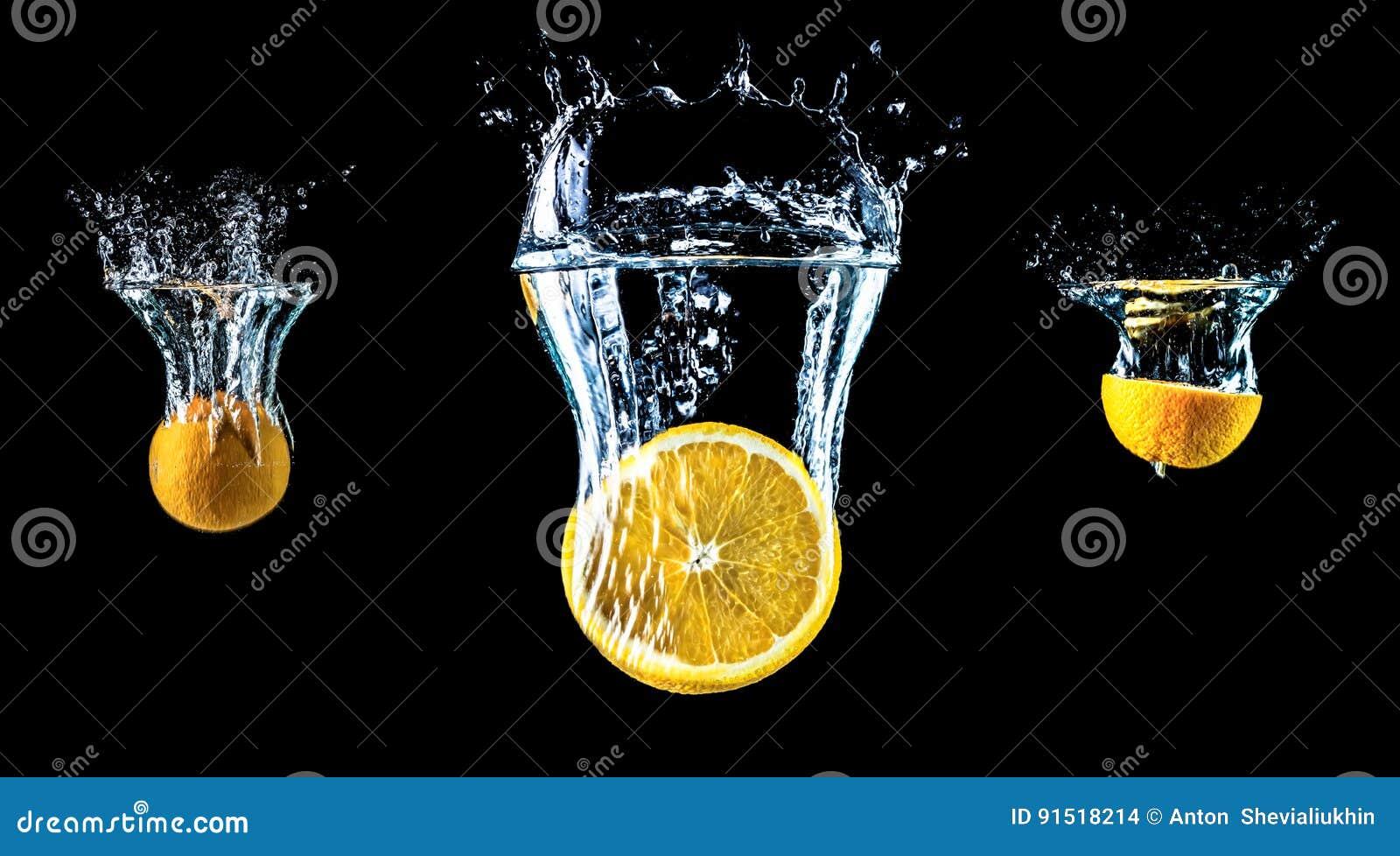 Sammansättning av tre apelsiner som faller in i vattennärbilden, makro, färgstänkvatten, bubblor, isolerad svart bakgrund