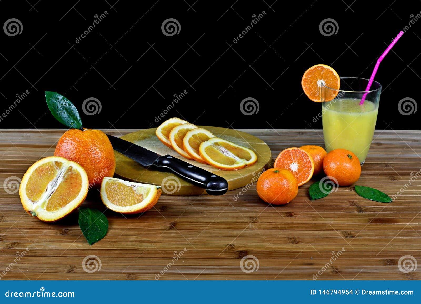 Sammansättning med den skivat citruns och exponeringsglas av orange fruktsaft