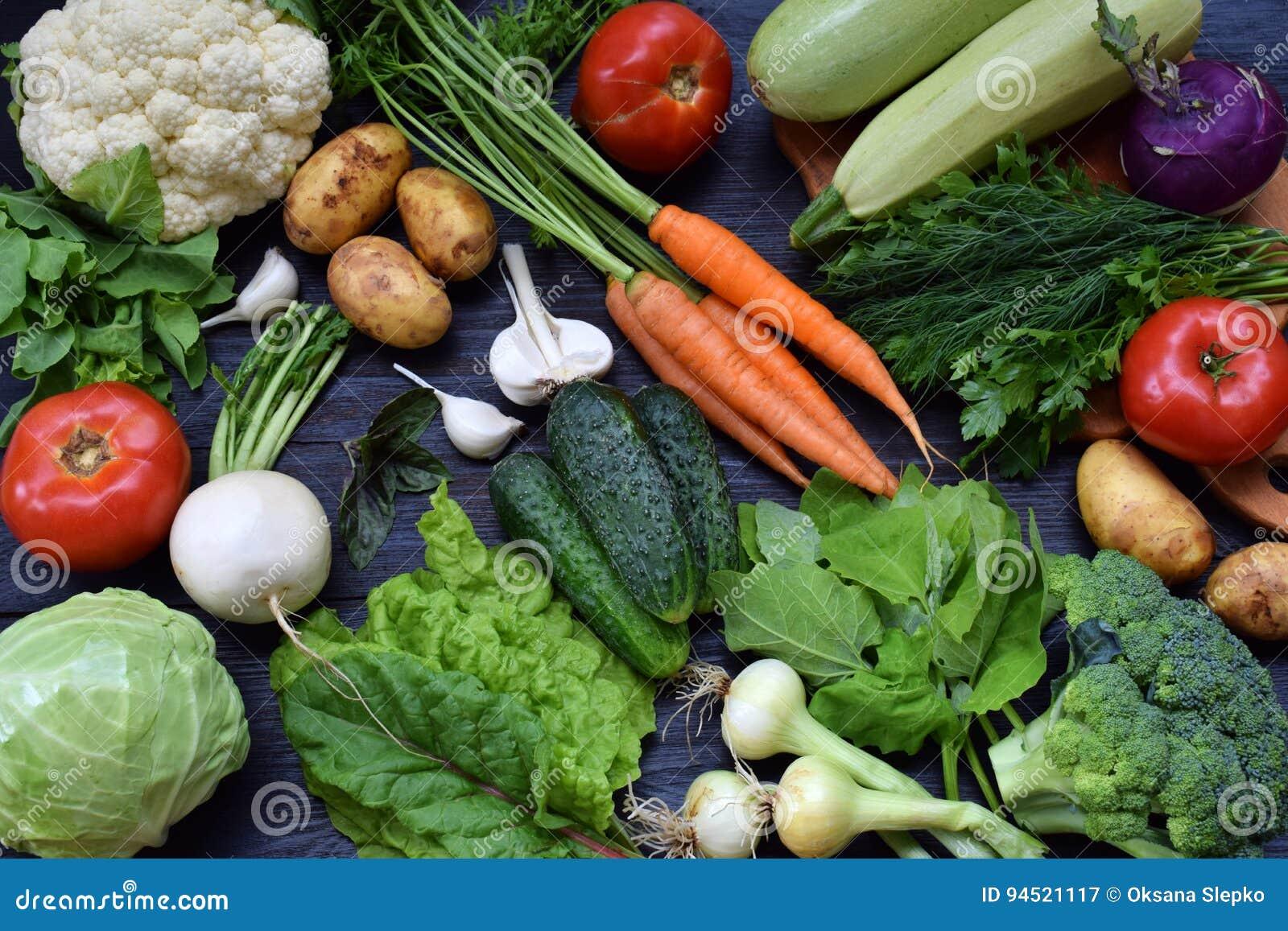 Sammansättning på en mörk bakgrund av organiska vegetariska produkter: gröna lövrika grönsaker, morötter, zucchini, potatisar, lö