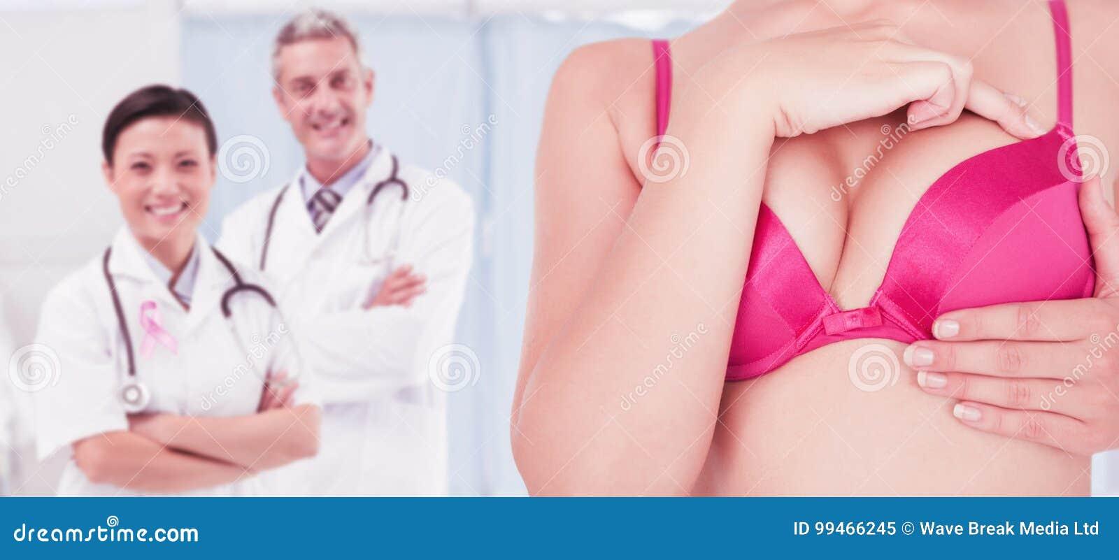 Sammansatt bild av det mitt- avsnittet av kvinnan i det rörande bröstet för rosa behå för cancermedvetenhet